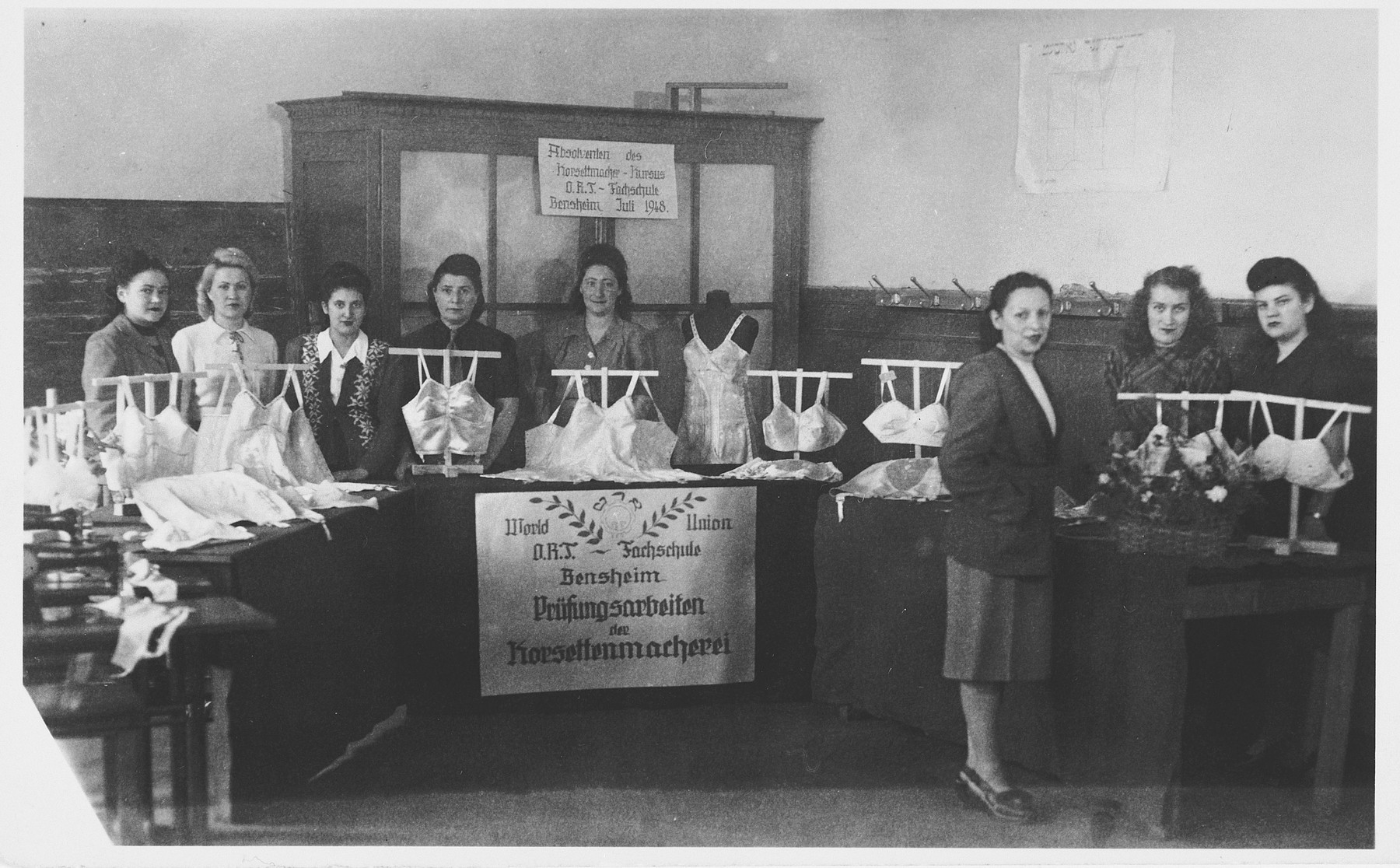 Women pose by a lingerie display at the ORT vocational training center in the Bensheim displaced persons' center.