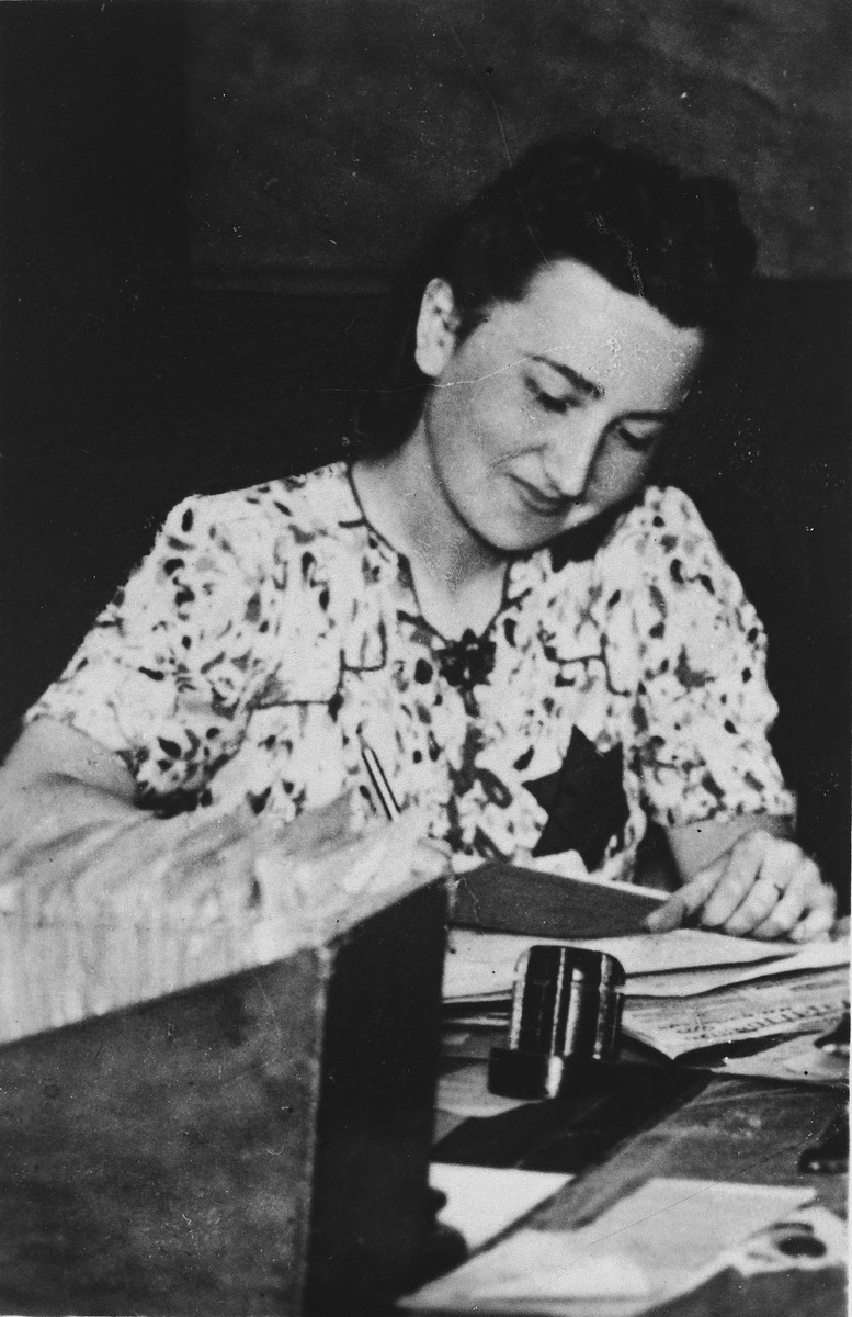 Rachela Pszerowska Ingster writes at a desk in the Bedzin ghetto.