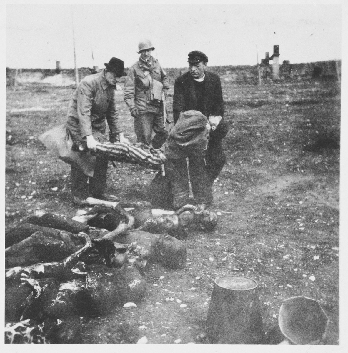 An American soldier supervisors two German civilians who have been forced to prepare corpses for burial at the newly liberated Buchenwald concentration camp.