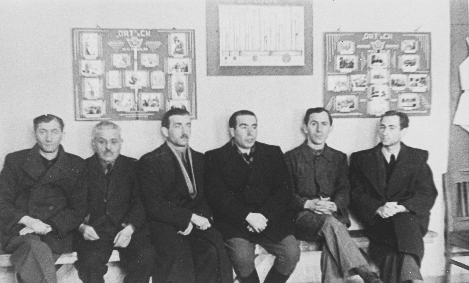 Edward Cittron and four other men sit in front of photo display in the ORT vocational school in Neu-Ulm.  Edward Cittron was the director of the school.  He is sitting in the center.  Second from the left is his father-in-law, Leon Grad and between them is Mr. Weinholz.