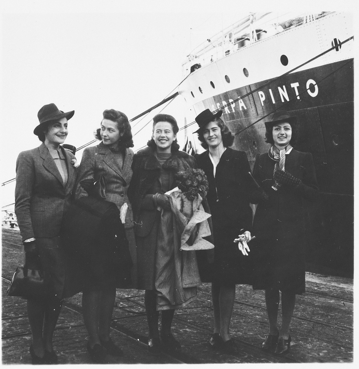 Five young, female Jewish refugees pose on the pier in the port of Lisbon before boarding the SS Serpa Pinto.  Among those pictured is Madeleine Hecht Feher, center holding a bouquet of flowers, surrounded by her co-workers from the American Joint Distribtuion Committee. On the far left is Lolita Goldstein, a JDC employee.