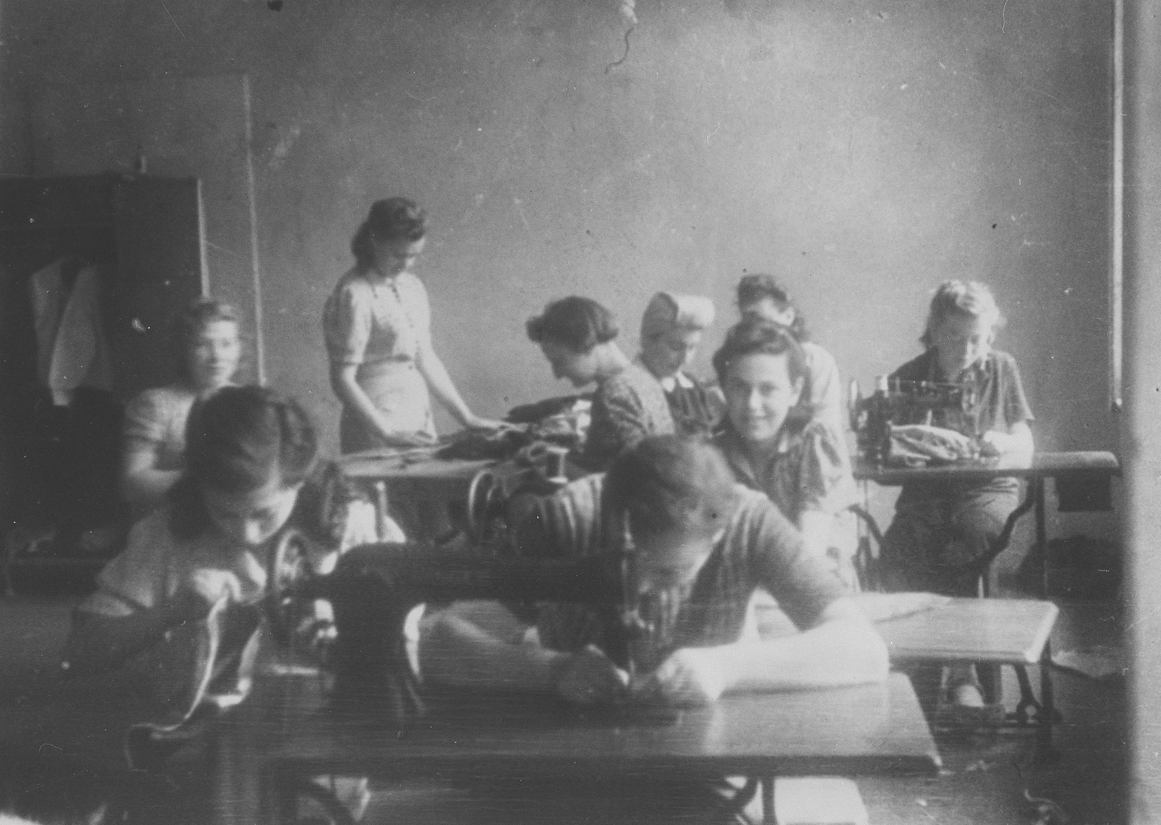 Jewish women learn to sew in a vocational training workshop in Lodz.  The woman in the back has her head fully covered since her hair still has not grown in since the war.
