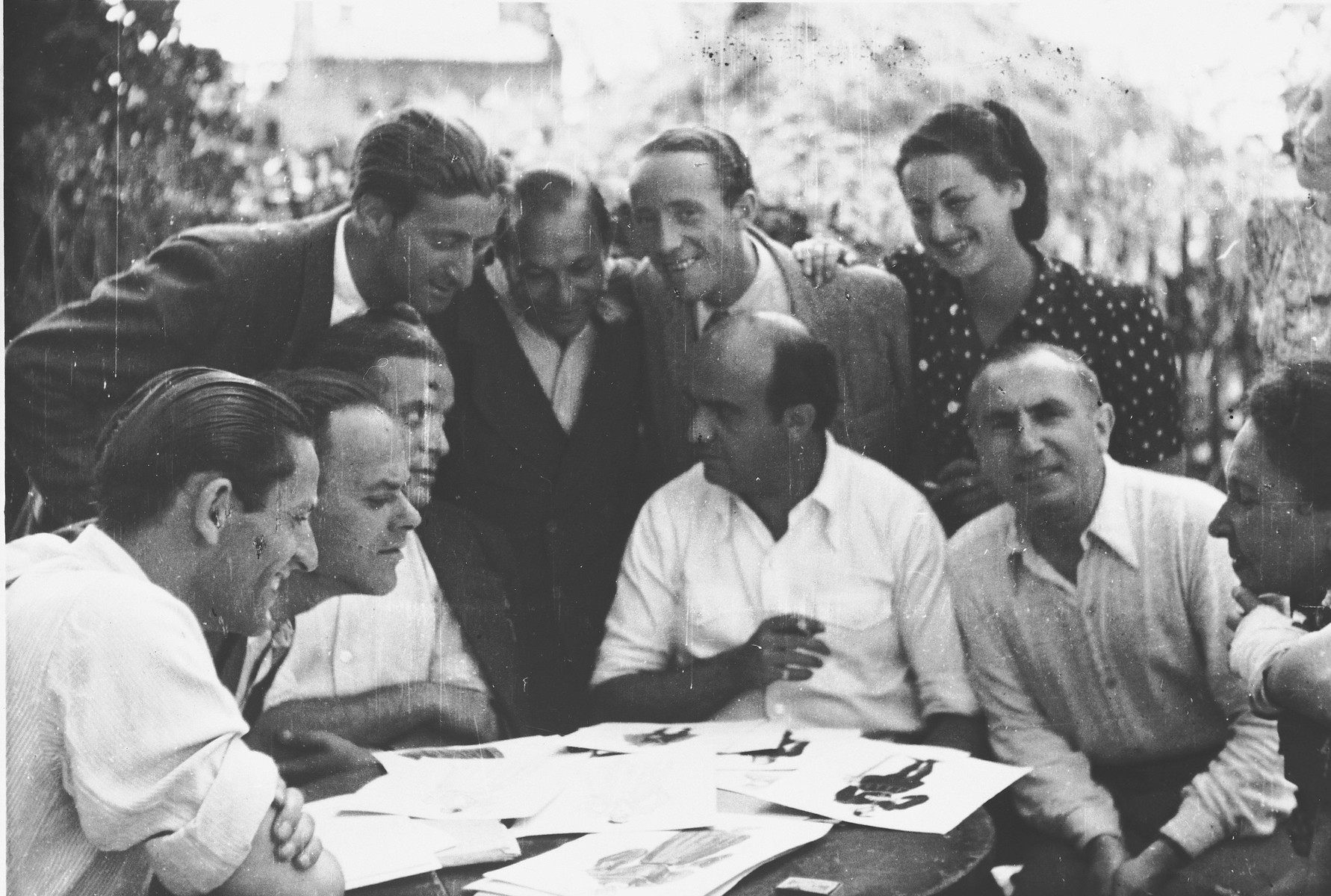Members of the MIT (Munich Jewish Theater) theatrical group examine costume designs while seated around a table in the Landsberg DP camp.