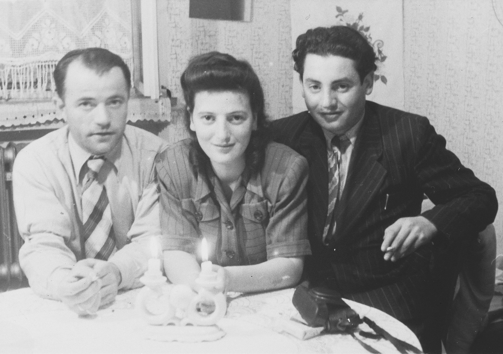 Three young Hungarian Jewish displaced persons sit around a table with lit candles.  Among those pictured is the donor, Sandor Berko, seated on the right.
