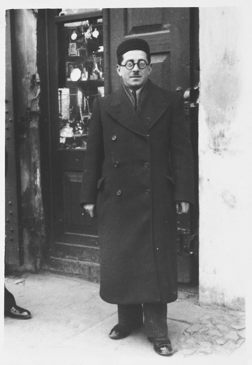 A religious Jew poses for a portrait in front of a store window.  Pictured is Hirsch Mayer Rabinowicz who perished during the Holocaust.