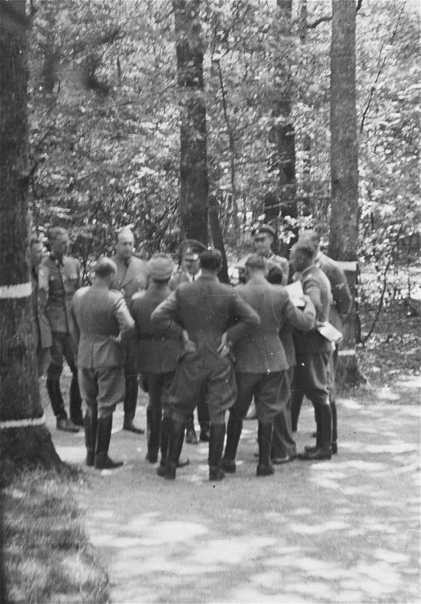 Adolf Hitler talks to other Nazi military officials at a wooded location.