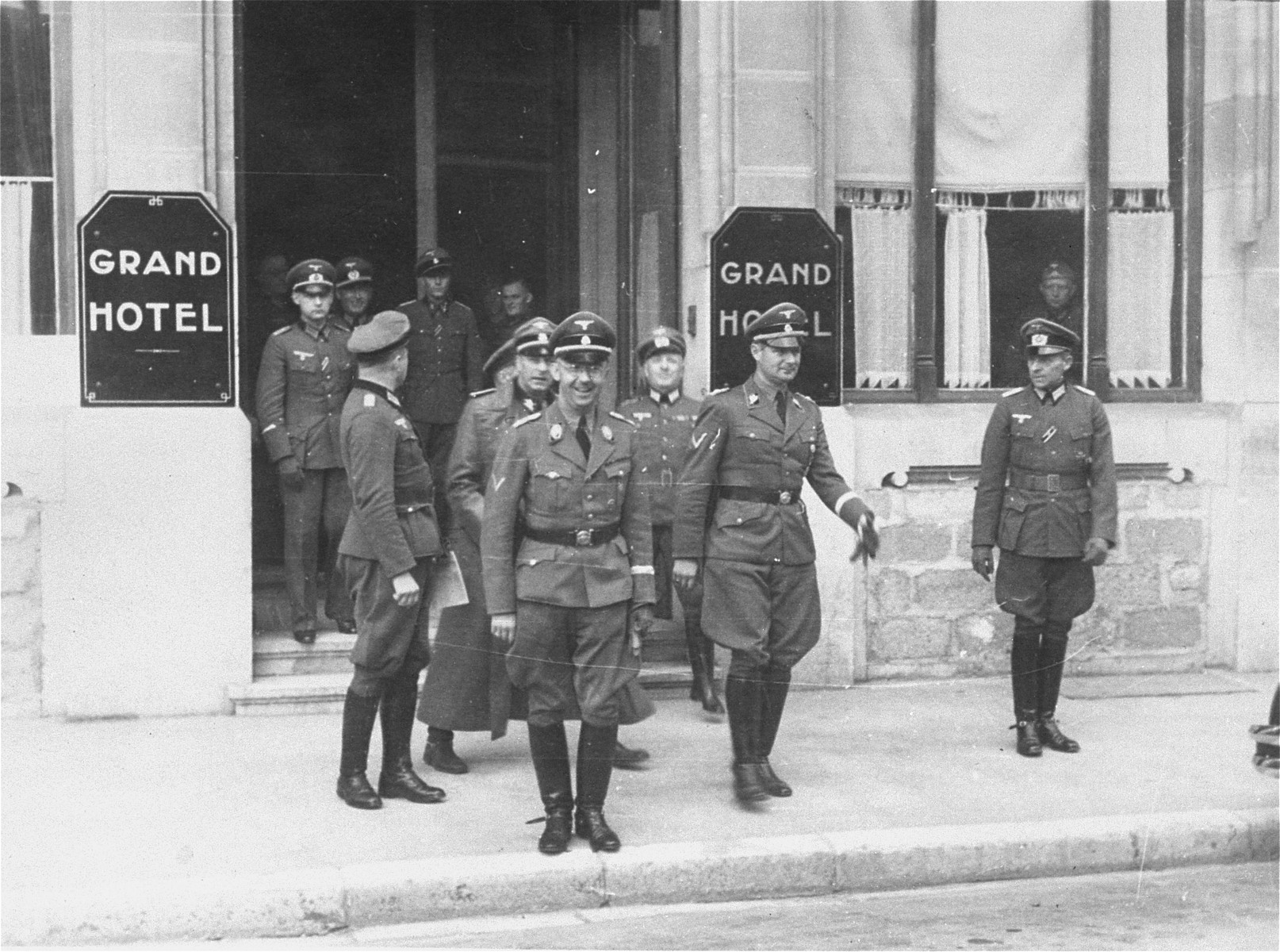 "Heinrich Himmler with other Nazi officials stand in front of the ""Grand Hotel"" in an unidentified location.   To the right of Himmler, and carrying gloves, is Karl Wolff.  The man behind Himmler is SS-Gruppenfuhrer Werner Lorenz."