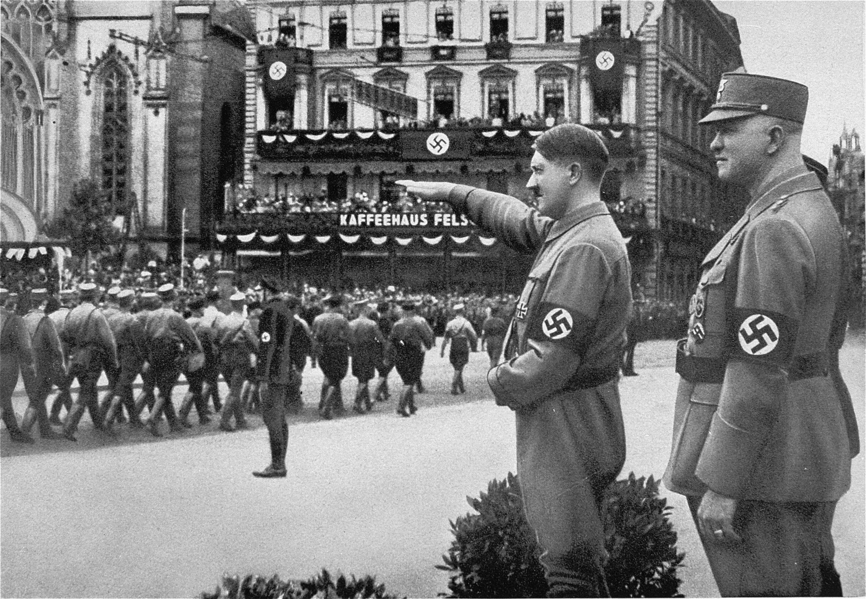 Adolf Hitler salutes passing SA troops while their commander, SA Reichstatthalter of Saxony, Mutschmann, looks on.
