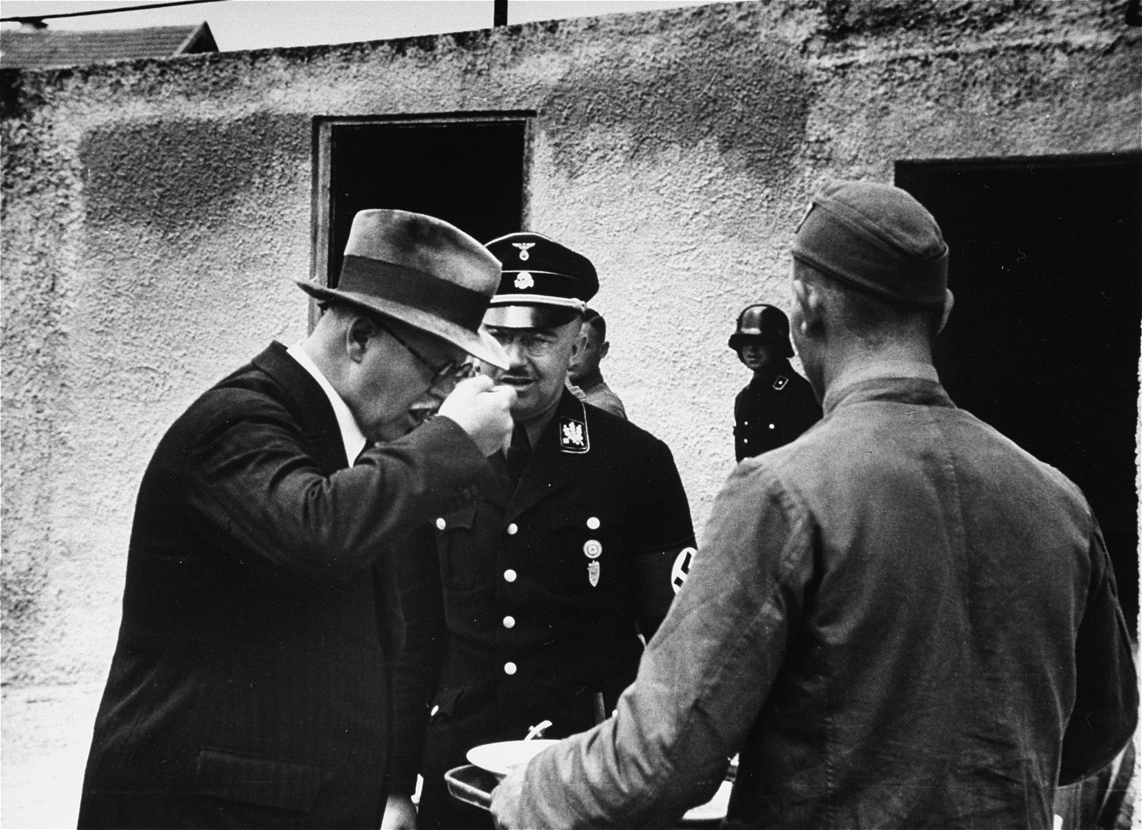 Heinrich Himmler watches an unidentified man, probably  Franz Xaver Schwarz,tasting food.  This image was taken from an album of SS photographs.