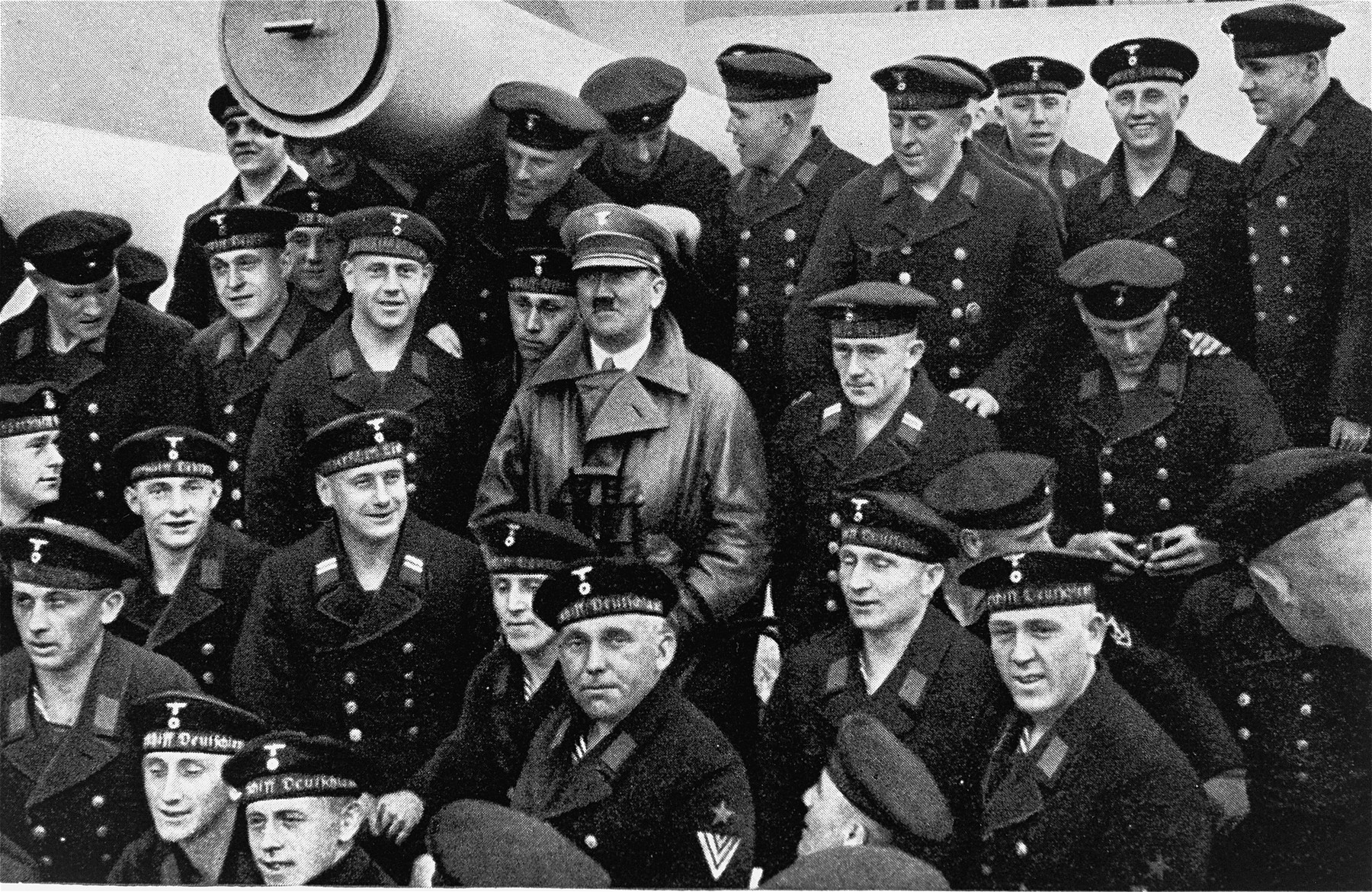 Adolf Hitler poses with a group of sailors aboard a German armored cruiser, the Deutschland.
