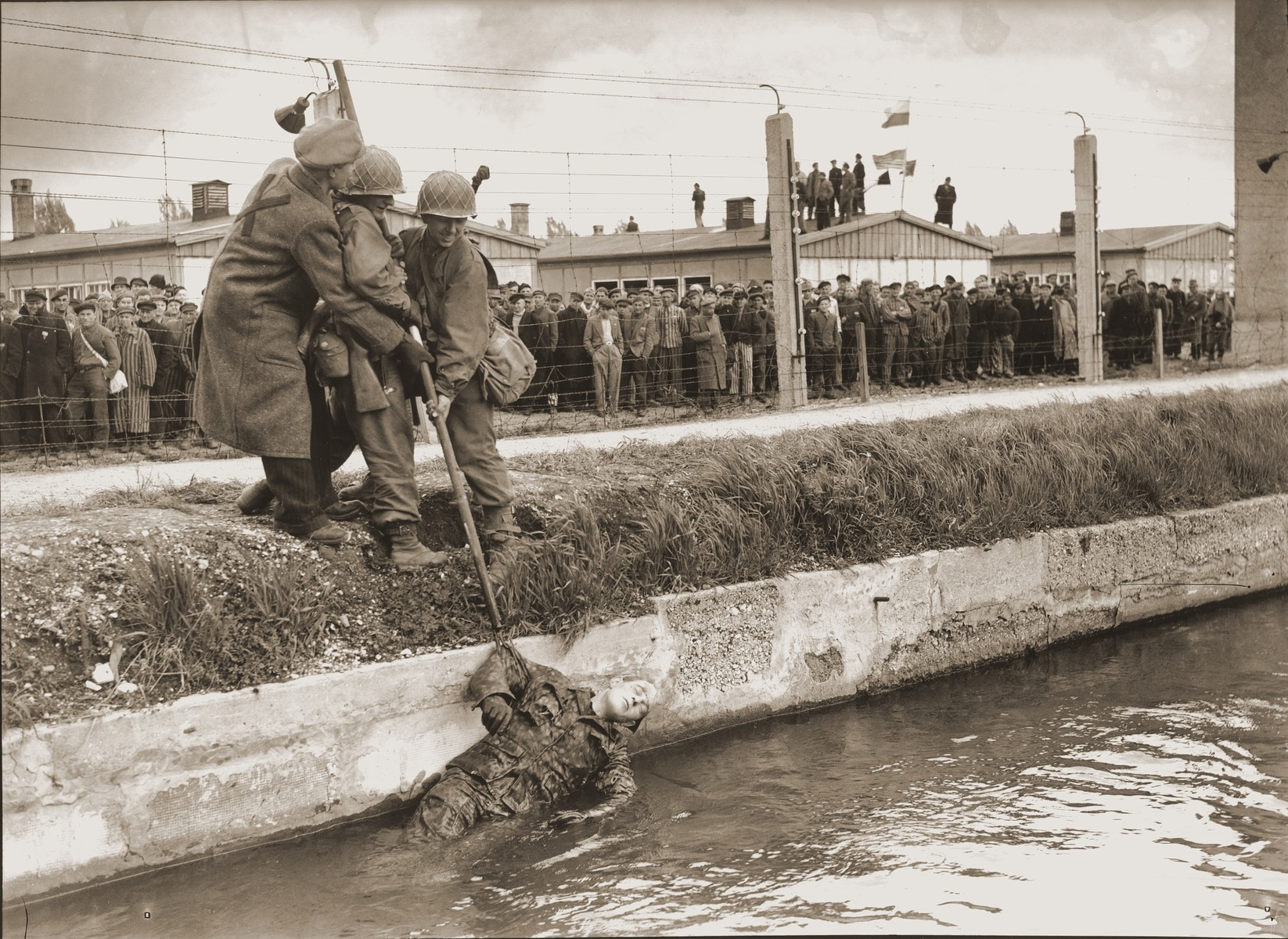 "Two soldiers from the 42nd Rainbow Division and a liberated prisoner fish the body of an SS guard out of the moat surrounding the Dachau concentration camp.   The original caption reads, ""Dachau Concentration Camp.  Horrors worse than those found in the German concentration camps of Buchenwald and Belsen were discovered in the stinking hell-hole of Dachau, captured by troops of the 42nd and 45th Infantry Divisions of the Seventh U.S. Army April 30, 1945.  More than 32,000 prisoners were liberated, among them some Englishmen, Canadians and Americans.  The camp was formally surrendered by an SS lieutenant carrying a white flag, accompanied by a Swiss Red Cross official, but SS troops opened fire as American troops approached the main entrance.  The Germans were shot down.  Three prisoners were electrocuted when they tried to burst through the electrified wire barrier to welcome the Americans.  SS guards opened fire on other prisoners who went wild with joy and rushed to meet the liberating troops.  Prisoners with access to records said 9,000 people died of hunger, disease or shooting within the past three months at Dachau.  Four thousand more perished during cold Winter months.  When Americans entered the camp, they found 50 open railway cars standing on a siding, apparently full of dirty clothing but actually found to contain hundreds of corpses piled on top of each other.  They also found a row of kennels where fierce dogs were kept to set after escaping men.  They discovered gas extermination chambers, incinerators full of naked bodies, bodies marked for dissection and the bodies of several small children.   This photo shows: Two soldiers of the 42nd ""Rainbow"" Division, Seventh U.S. Army, are assisted by a liberated political prisoner as they pull the body of a dead Nazi SS guard from the moat surrounding the camp.  Other liberated prisoners in the background watch from behind the former electrified fence.  Some SS guards were killed and thrown into the moat by the liberated prisoners, others by American soldiers."""