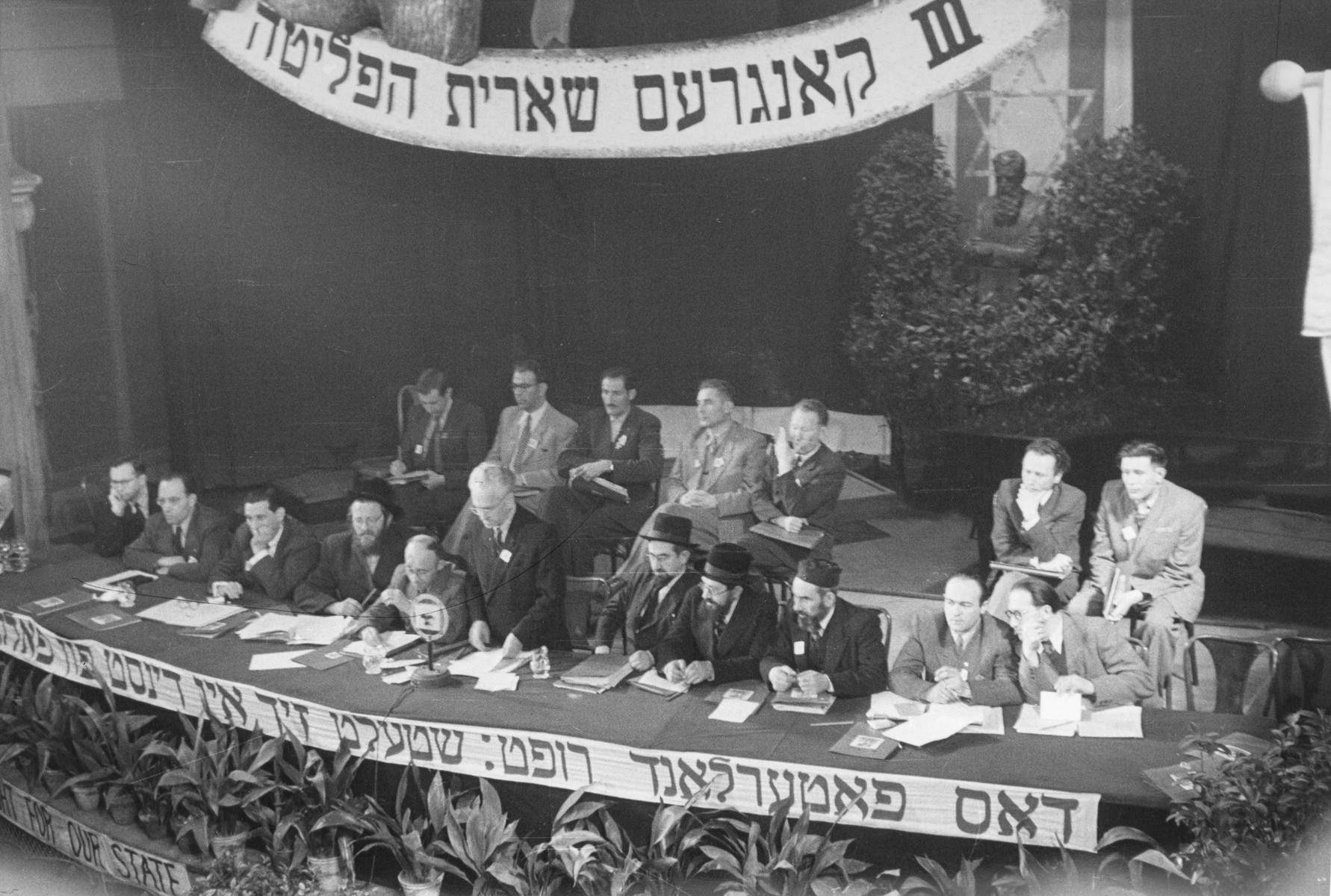 """View of the dais at the Third Congress of the Central Committee of the Liberated Jews in the U.S. Zone held in Bad Reichenhall.    The Yiddish banner on the podium reads, """"The Fatherland calls; offer your service to the people."""""""