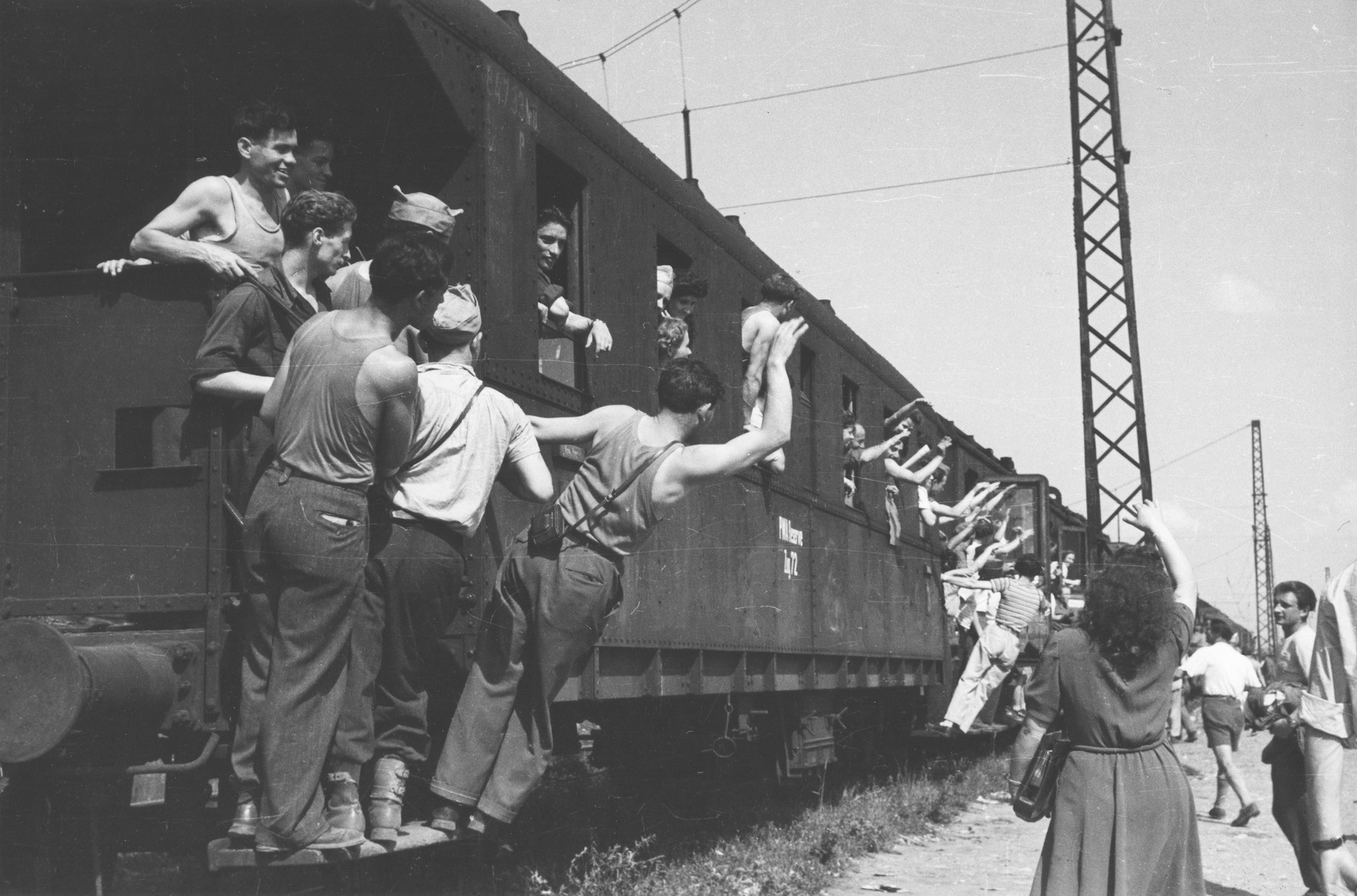 Jewish DPs on board a train wave good-bye to friends and relatives as they leave Germany for France en route to Israel.