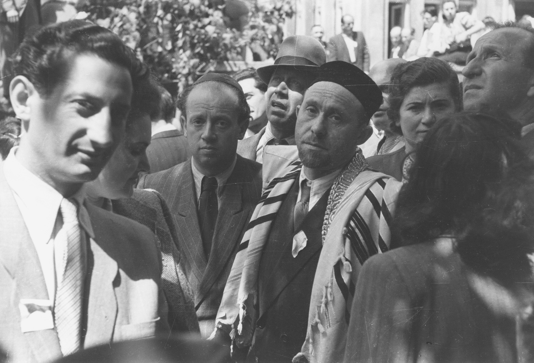 Cantor Jousha Wieder, wearing a tallit, stands among a crowd of Jewish displaced persons at a rally for the new State of Israel in Munich.