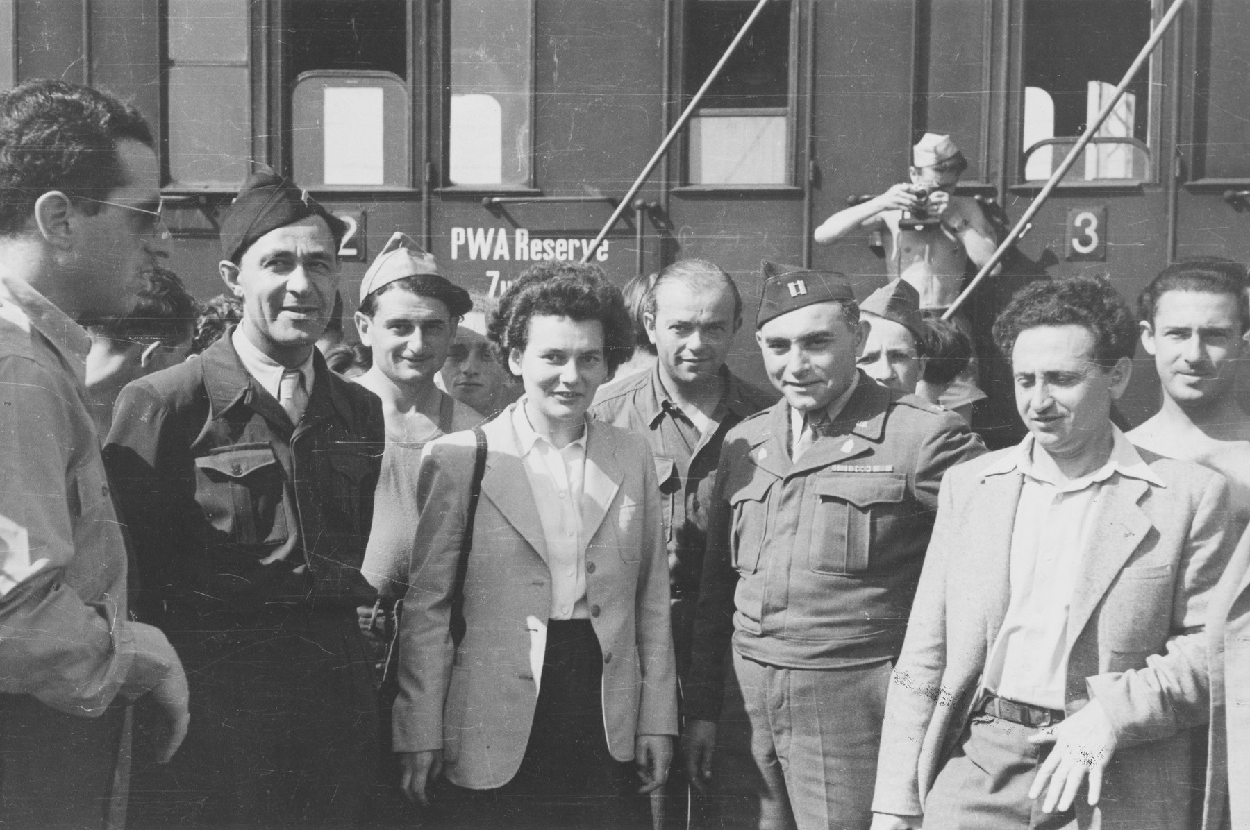 Chaplain Levaser and Jewish Brigade soldiers are photographed at the train station where they have come to bid farewell to a group of DPs who are leaving for Marseilles on the first leg of their journey to Israel.