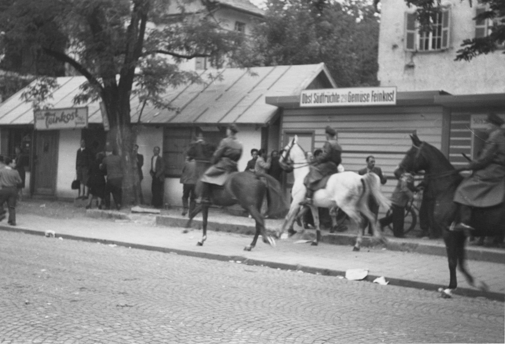 German police on horseback conduct a raid to suppress Jewish black market activity on the Moehlstrasse in Munich.