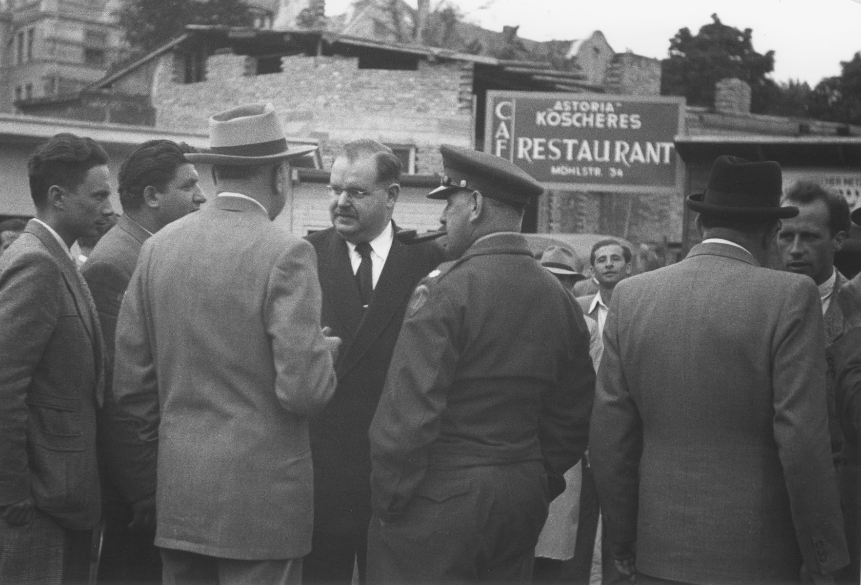 Philipp Auerbach talks to a group of men, including representatives of the military government outside the Astoria Kosher restaurant on the Moehlstrasse.