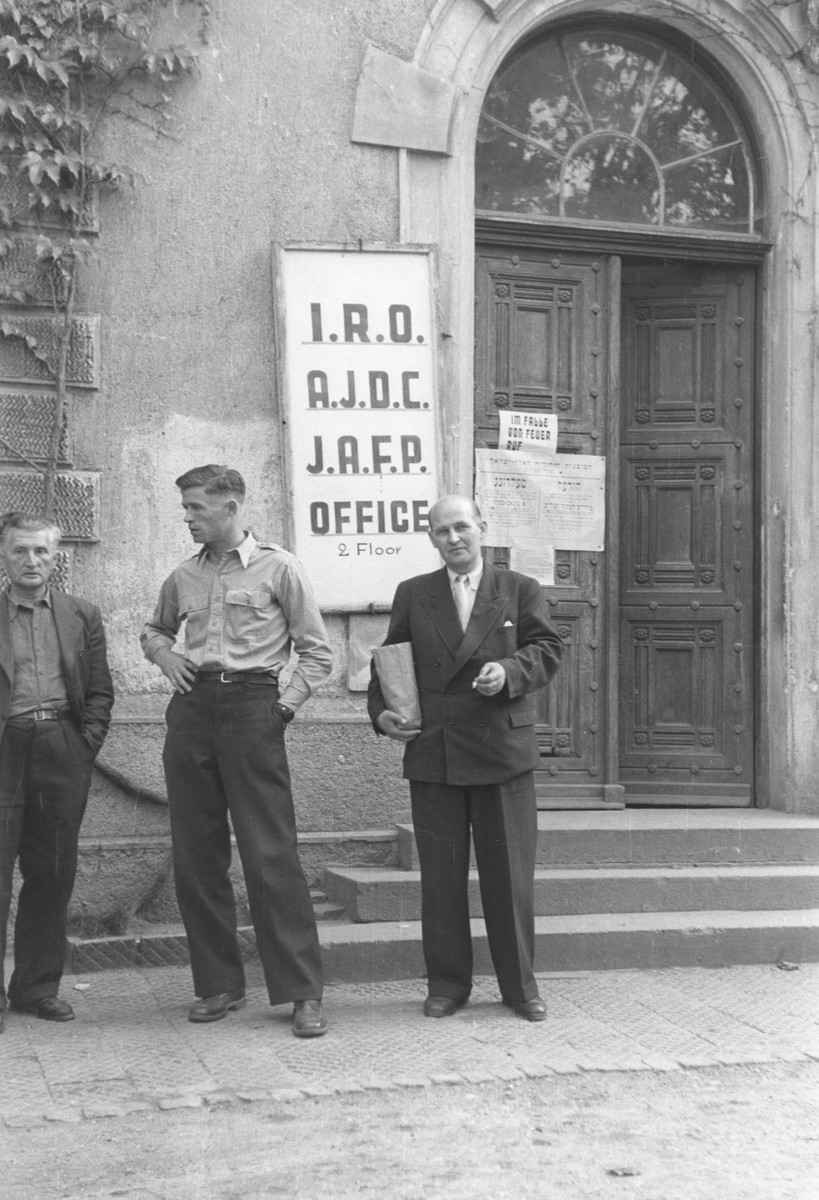 Three men stand outside a building in the Munich Warner-Kaserne (barracks) displaced persons transit camp where the offices of the IRO (International Refugee Organization,  AJDC (American Joint Distribution Committee) and JAFP (Jewish Agency for Palestine) were located.  Among those pictured is Dr. Schmonowicz (sp?).