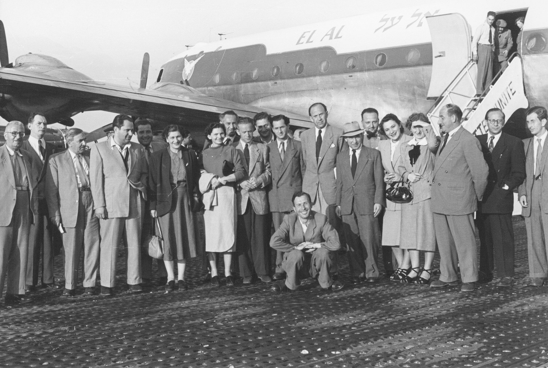 Jewish DPs pose in front of an El Al airplane prior to their departure for Israel.  Among those pictured is Isak Bank (tallest man to the right of center).