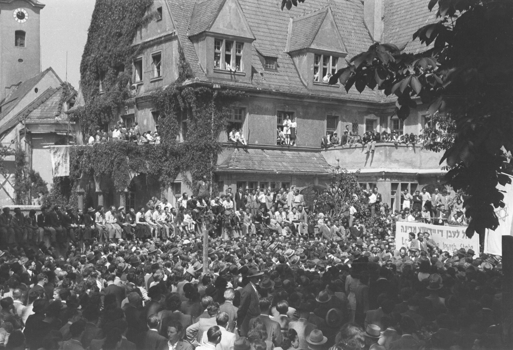 "Thousands attend a rally celebrating the founding of the State of Israel, outside the headquarters of the Central Committee of the Liberated Jews in the US Zone of Germany located on the Moehlstrasse in Munich.  The Yiddish banner reads: ""Long live the Jewish State."""
