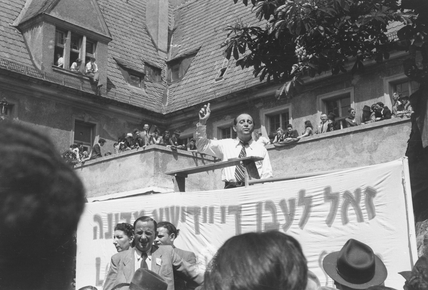 "A speaker addresses a crowd at a rally celebrating the founding of the State of Israel, outside the headquarters of the Central Committee of the Liberated Jews in the US Zone of Germany located on the Moehlstrasse in Munich.  The Yiddish banner reads: ""Long live the Jewish State."""
