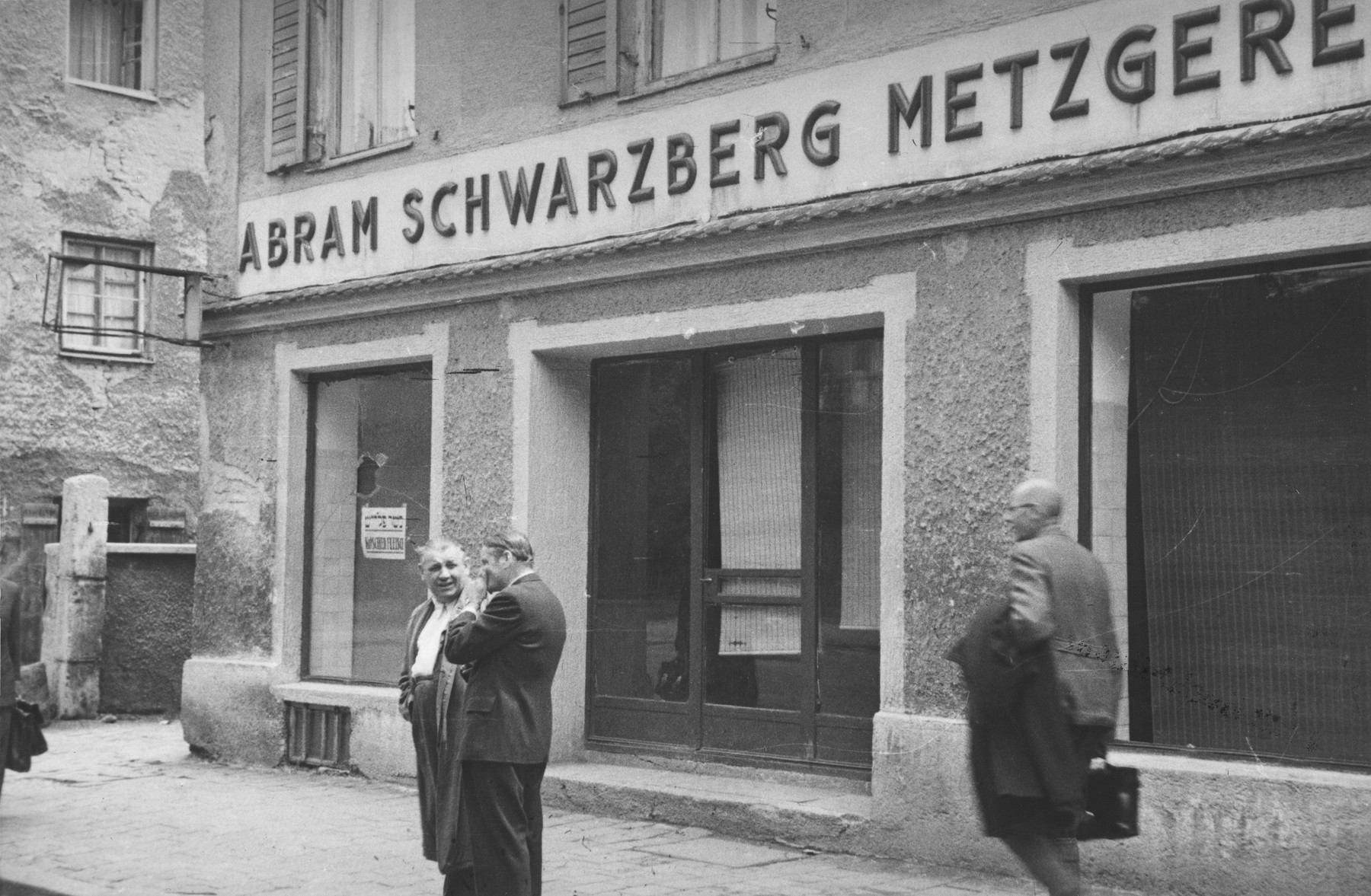 Two men stand outside a kosher butcher shop on the Ismaningerstrasse in Munich that was vandalized in an anti-Semitic attack.