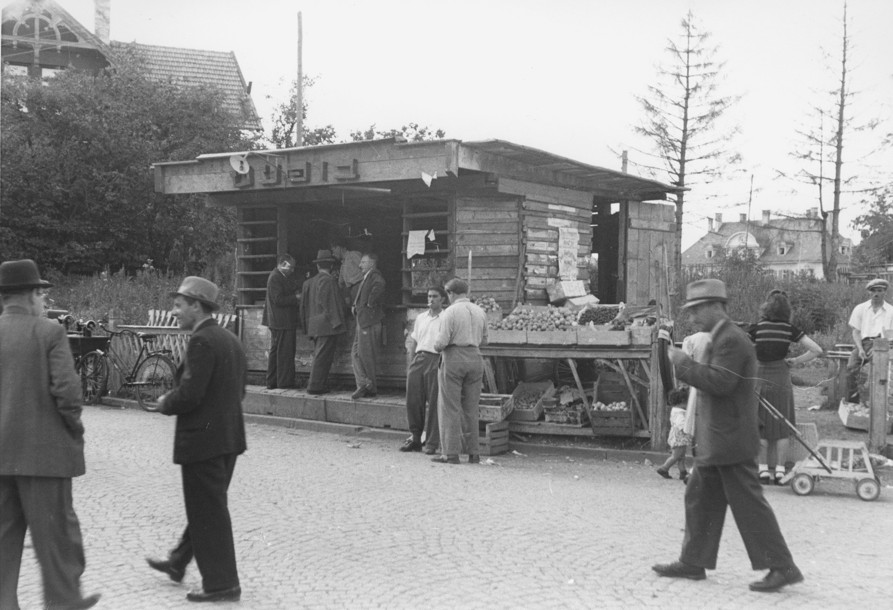 """Jewish DPs patronize a kosher food stand in the Warner-Kaserne displaced persons transit camp in Munich.  The Hebrew sign above the food stand reads """"Buffet."""""""