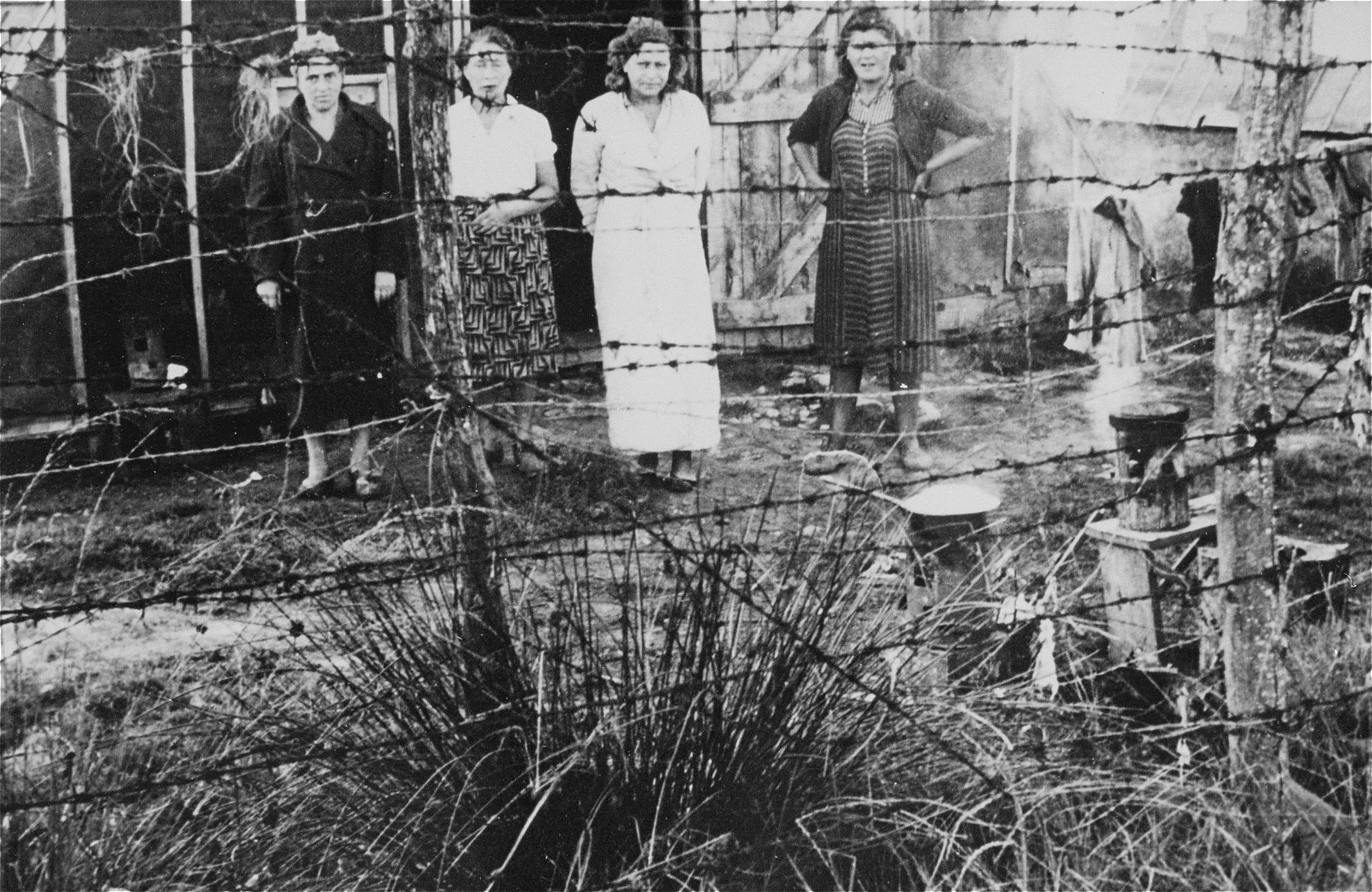 """Four female prisoners stand outside a barracks behind a barbed-wire fence in """"Ilot L"""" at the Gurs transit camp.  This photograph was shot secretly by Alice Resch-Synnestvedt, a relief worker from the American Friends Service Committee, during her stay at the camp."""