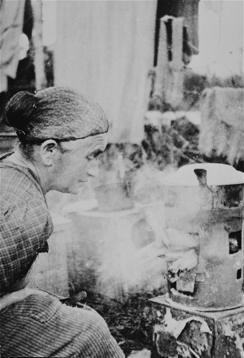 Mrs. Althausen from Mannheim, a prisoner in Gurs, cooks soup on a makeshift stove.    This photograph was shot secretly by Alice Resch-Synnestvedt, Adnish social worker, during her stay in Gurs as a delegate of the American Friends Service Committee.