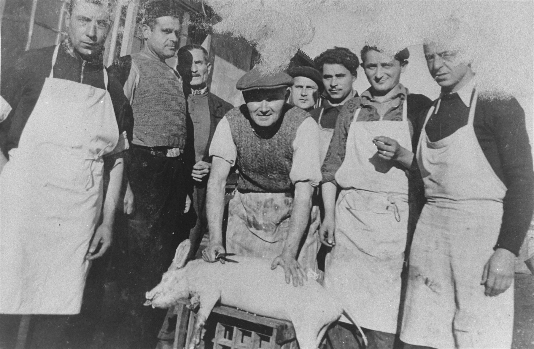 A group of kitchen workers in the Gurs concentration camp pose with a slaughtered pig.  Siegfried Lindheimer is pictured in the center behind the pig.