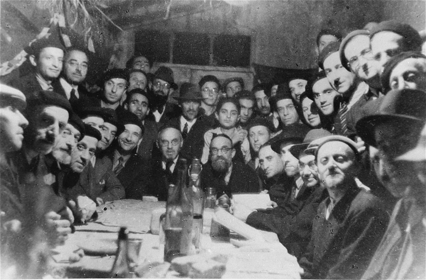 Jewish prisoners celebrate the holiday of Hoshanah Rabbah in a Sukkah in the Les Milles transit camp.    Among those pictured is Rabbi Siegmund Marx (left of center, wearing a beard), a Jewish refugee from Speyer, Germany.