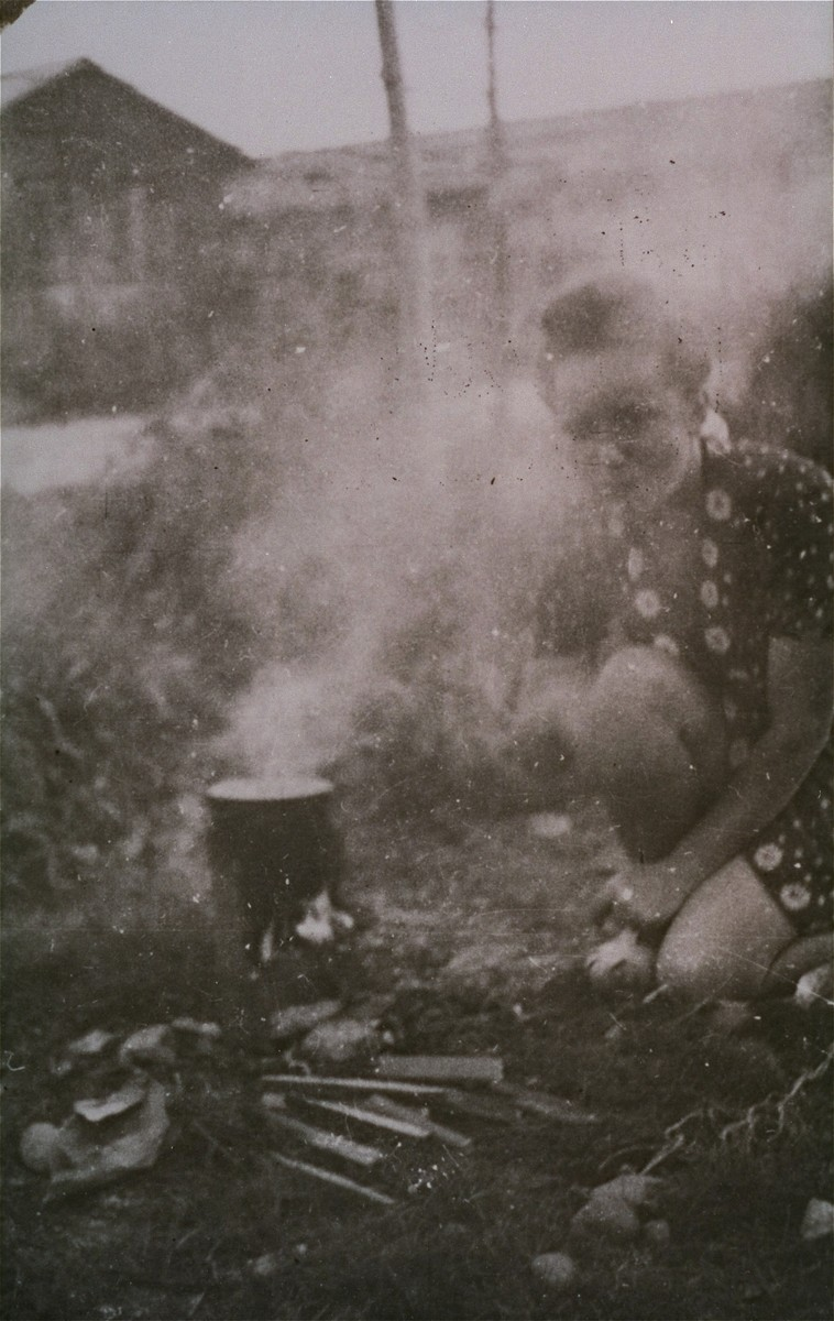 A woman prisoner in Gurs cooks on an open fire in Ilot L.  This photograph was shot secretly by Alice Resch-Synnestvedt during her stay in Gurs as a delegate of the American Friends Service Committee.