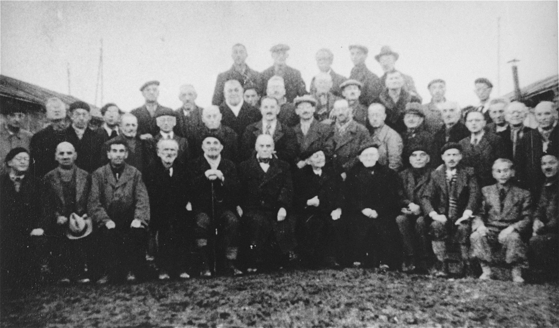 Group portrait of Jewish inmates in the Gurs internment camp.    Among those pictured are: Oskar Wachenheimer (back row, left), Hugo Wachenheimer (second row, fourth from the right), Julius Wachenheimer (front row, sixth from the right).  Hugo and Oskar perished in Auschwitz, and Julius died in the Noe internment camp.