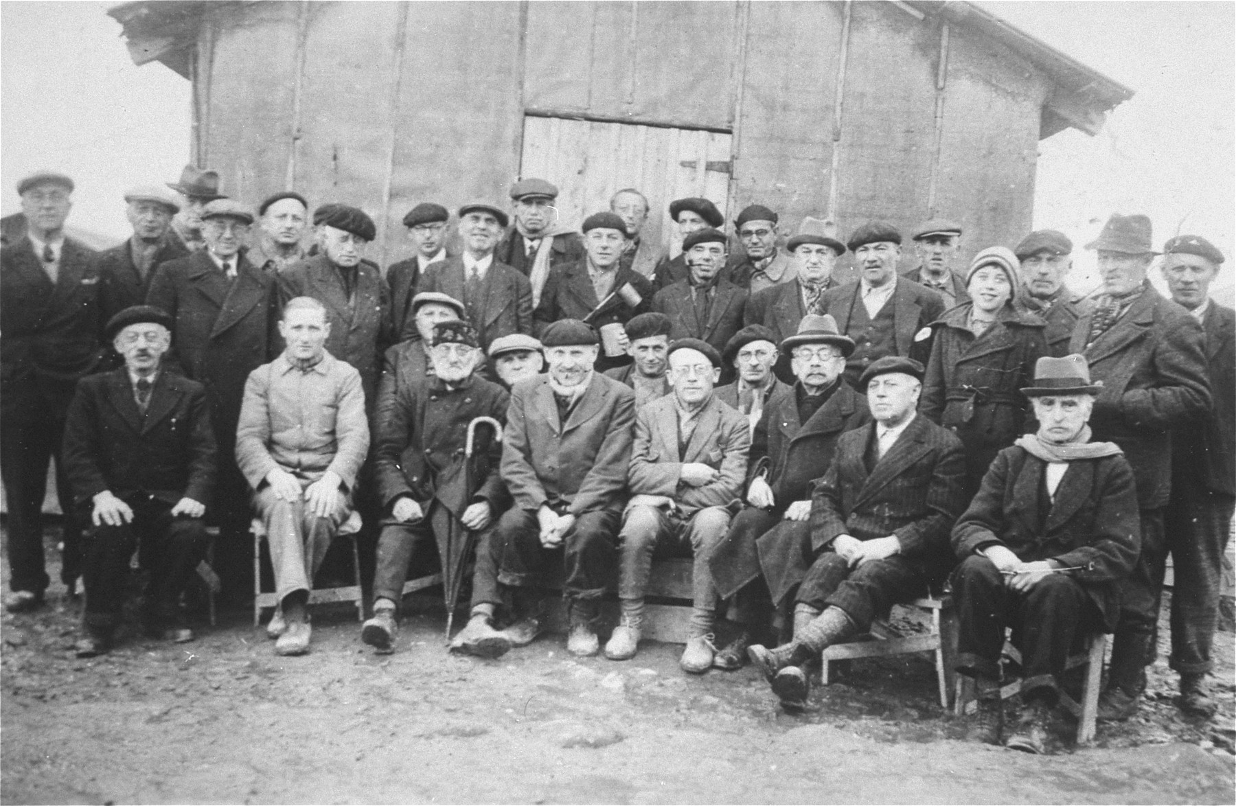 Group portrait of Jewish prisoners in the Gurs transit camp.    Samuel Liebermensch is pictured  at the center.  Hugo Mayer is seated on the lower right.  Siegfried Lindheimer is pictured in the first row , second from the left.