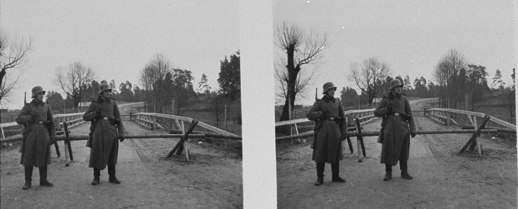 Stereoscopic photograph of two German sentries standing guard in front of a gate along the demarcation line between Soviet and German occupied Poland.