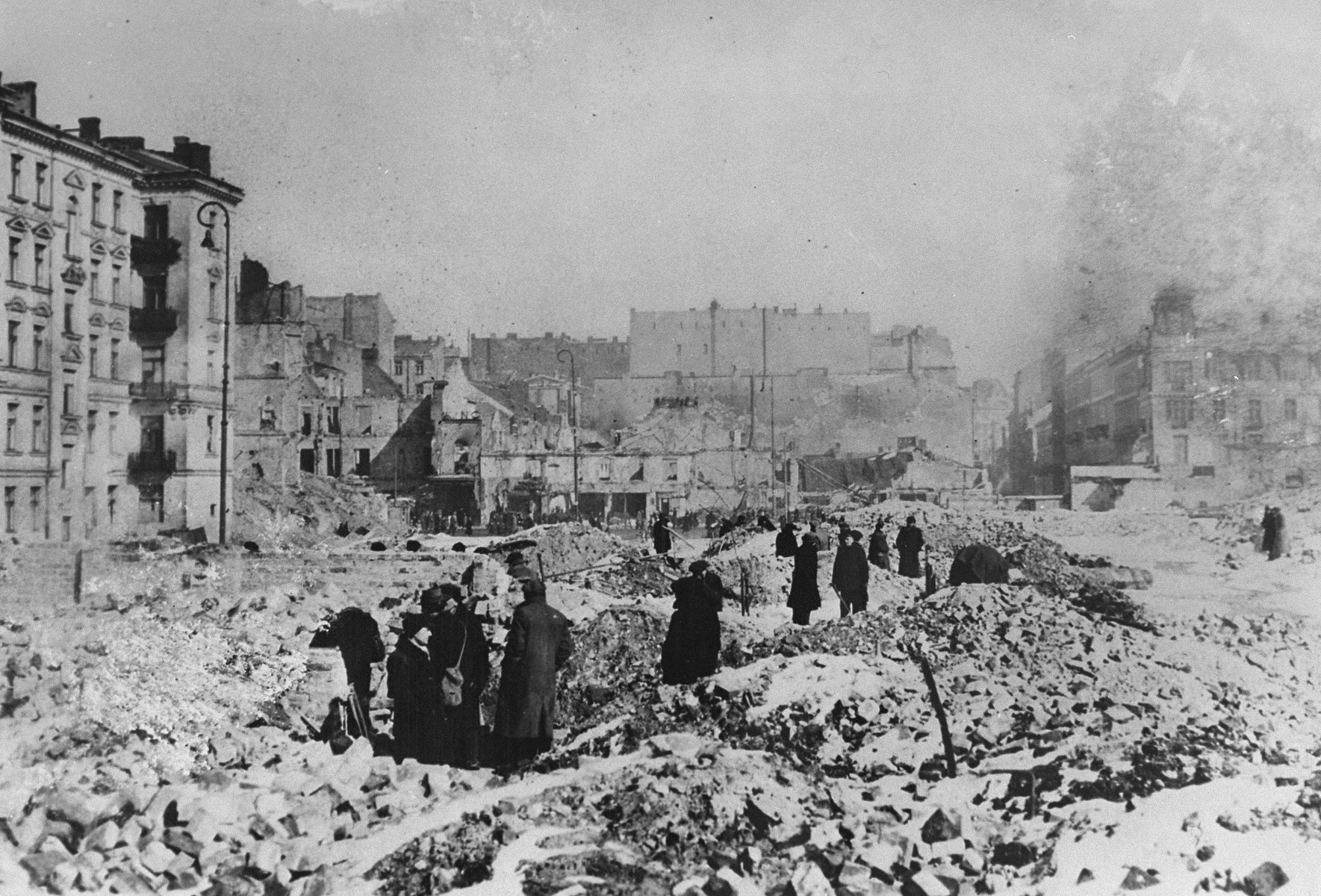 Local inhabitants wade through ruins in Warsaw following the surrender of the city.