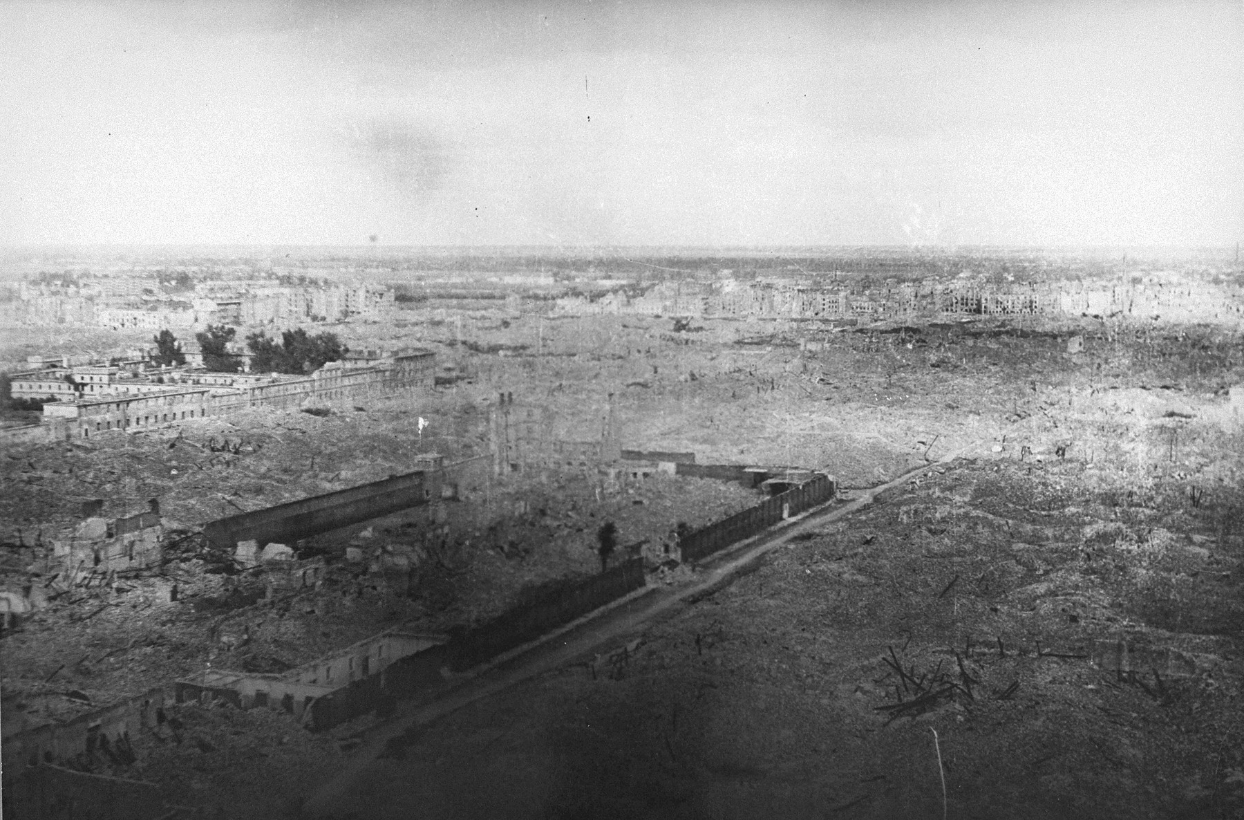 View of the ruins of the Warsaw ghetto.    Pictured in the middle are the walls of the Pawiak prison.  Visible on the far left is the Gesiowka prison.