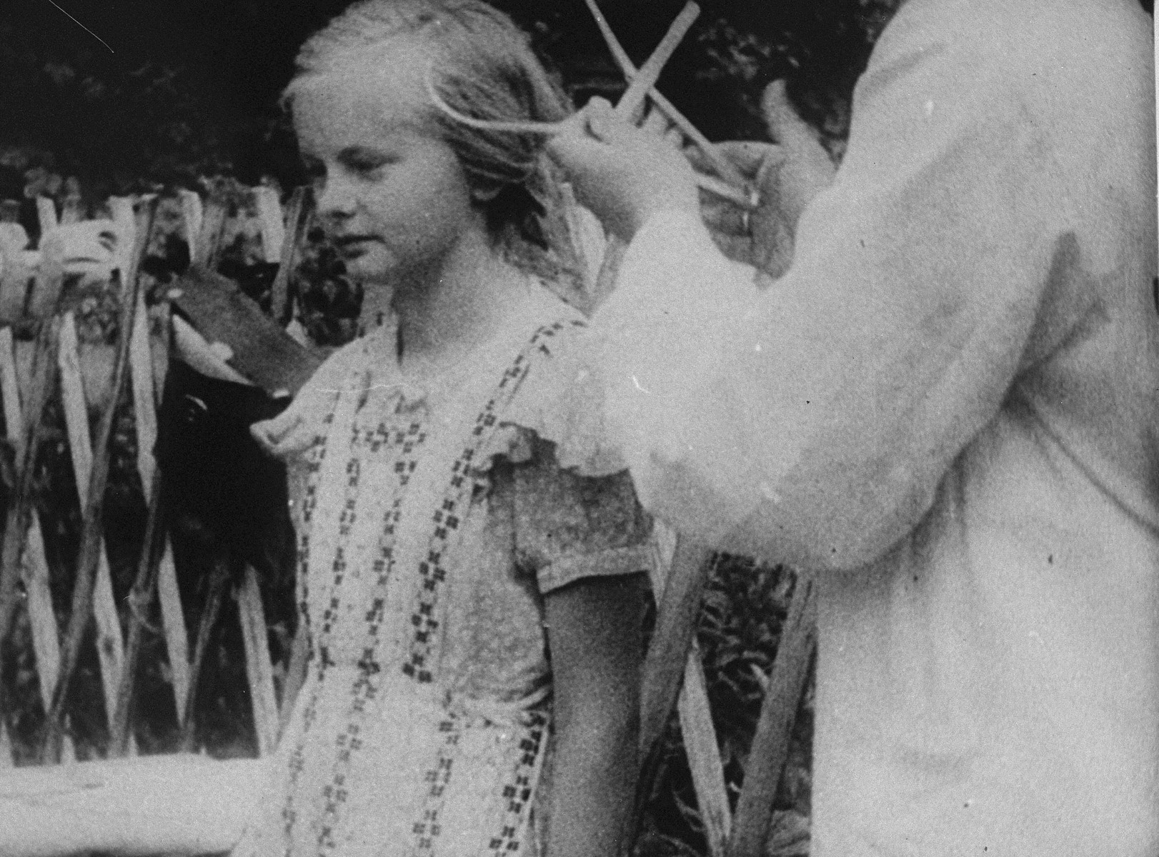The head of a young Polish girl is measured using a caliper during her racial examination by German authorities.