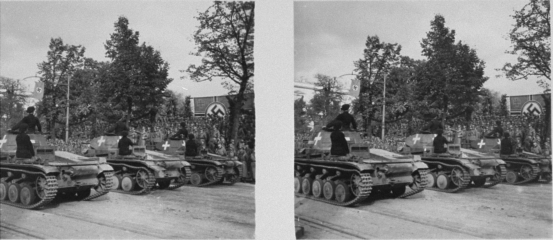 Stereoscopic photograph of German tank drivers turning to face a saluting Adolf Hitler, as they roll past the speakers' podium, during a victory parade in Warsaw celebrating the German conquest of Poland.
