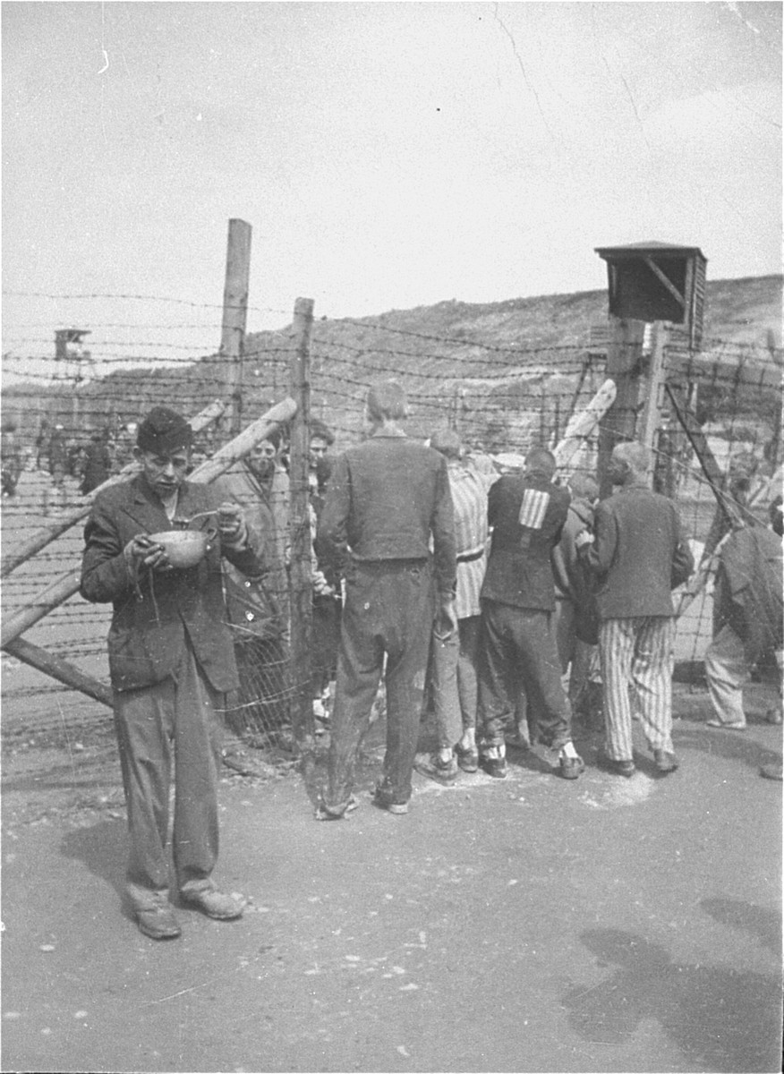 """Male and female Mauthausen survivors converse with one another through the barbed-wire fence that separates the """"sick camp"""" from the other sections of the camp."""