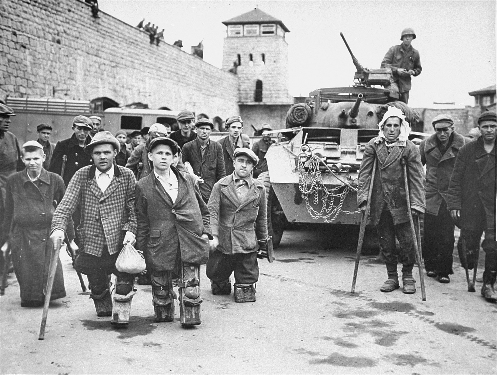 Disabled Polish and Russian survivors stand in front of a tank from the 11th Armored Division, Third U.S. Army, in the Mauthausen concentration camp.