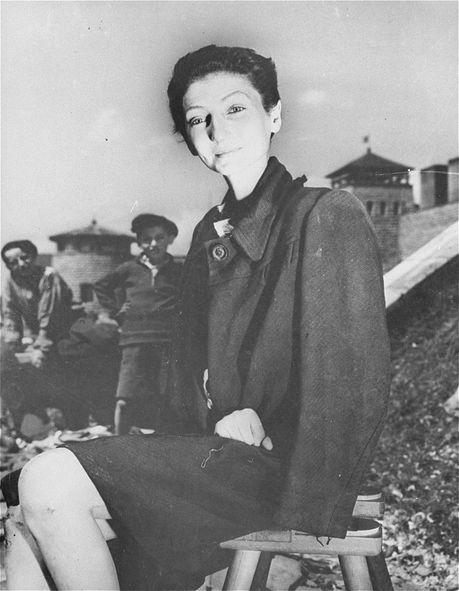 The Hungarian Jewish stage actress from Budapest, Livia Nador, sits outside on a stool at the newly liberated Mauthausen concentration camp.