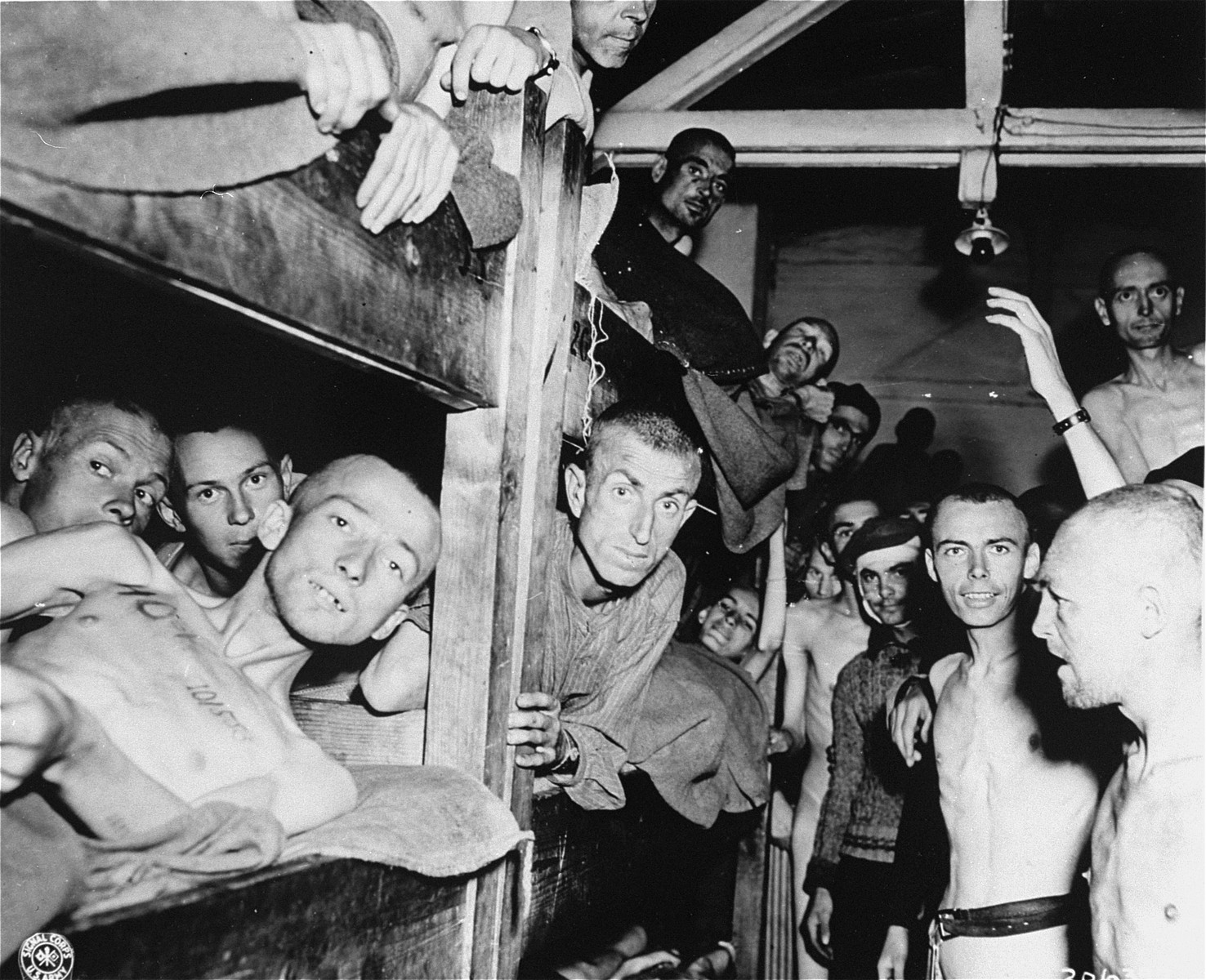 Survivors in a barracks in Mauthausen.  Note the tattoo on the chest of the man in the left foreground.