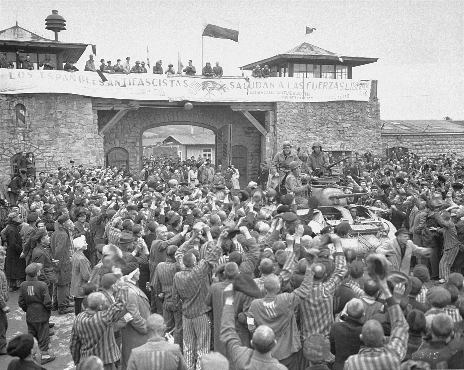 "Mauthausen survivors cheer the soldiers of the Eleventh Armored Division of the U.S. Third Army one day after their actual liberation.   The banner reads: ""The Spanish Anti-Fascists Salute the Liberating Forces.""  According to Pierre Serge Choumoff, a survivor of Mauthausen and Gusen, this event was recreated at the request of a senior American officer.  The photographer Francisco Boix can be seen with his camera standing on top of the entrance.  According to the 11th Armored Division website the solders are John Slatton (back left), Jerome Rosenthal (back right), William Picket (left) and Edward Czarnowski (driver).  Alternatively Robert Mordis, a Jewish soldier from Natick Massachusetts, may be on the upper left side of the tank, and another soldier may be Alfred Paliani."