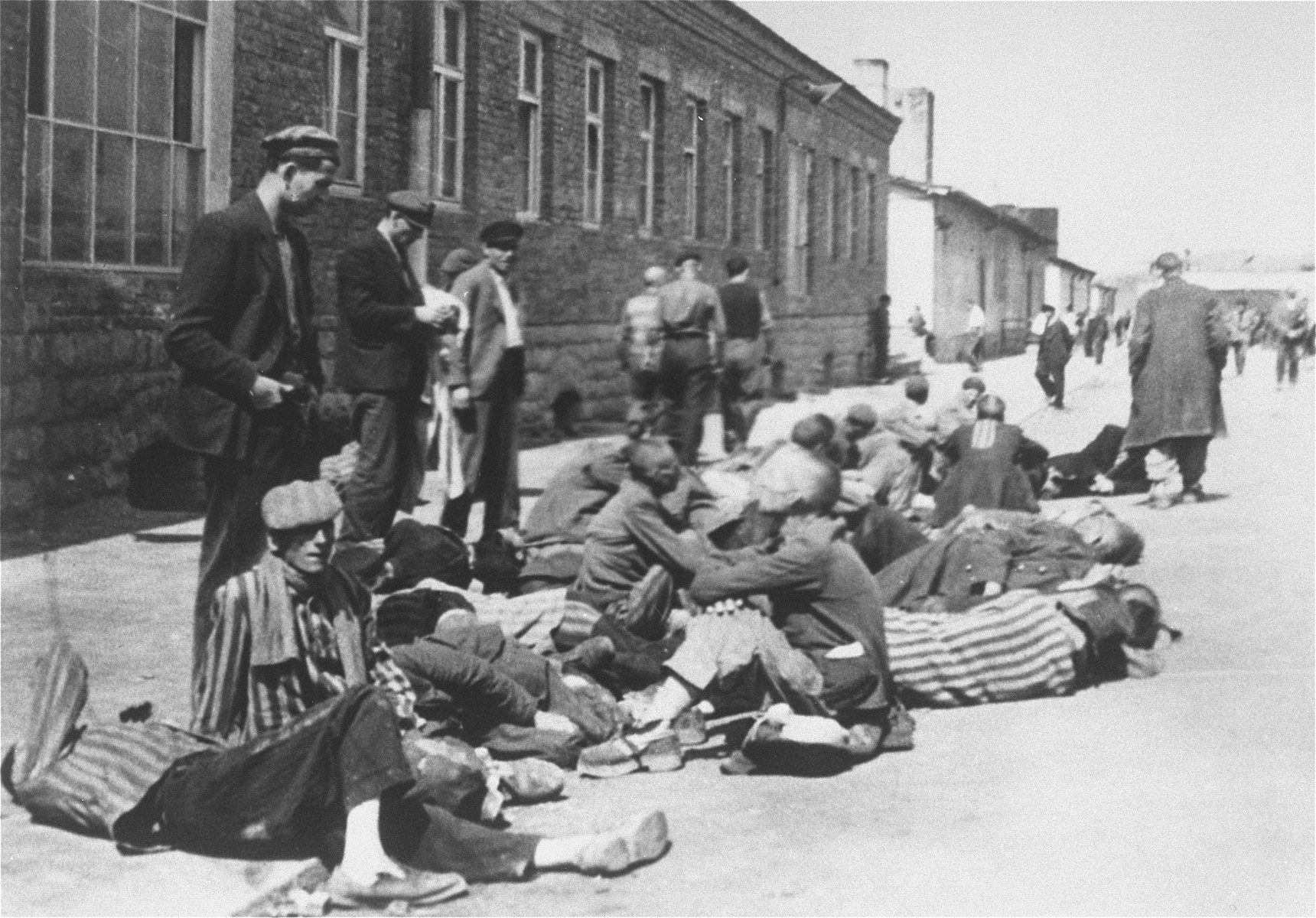 Survivors in Mauthausen rest outside a barrack after the liberation of the camp.