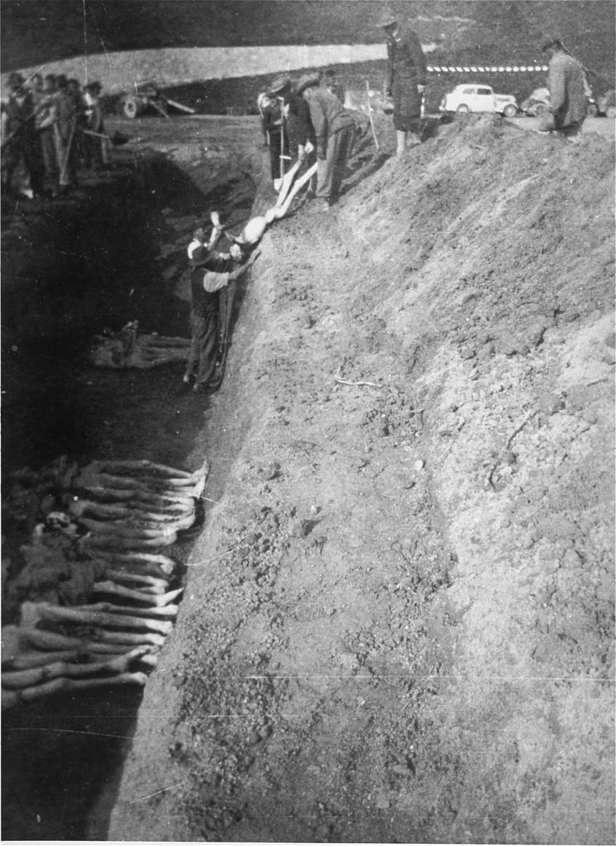 Austrian civilians drop the bodies of former prisoners into a mass grave at Mauthausen.