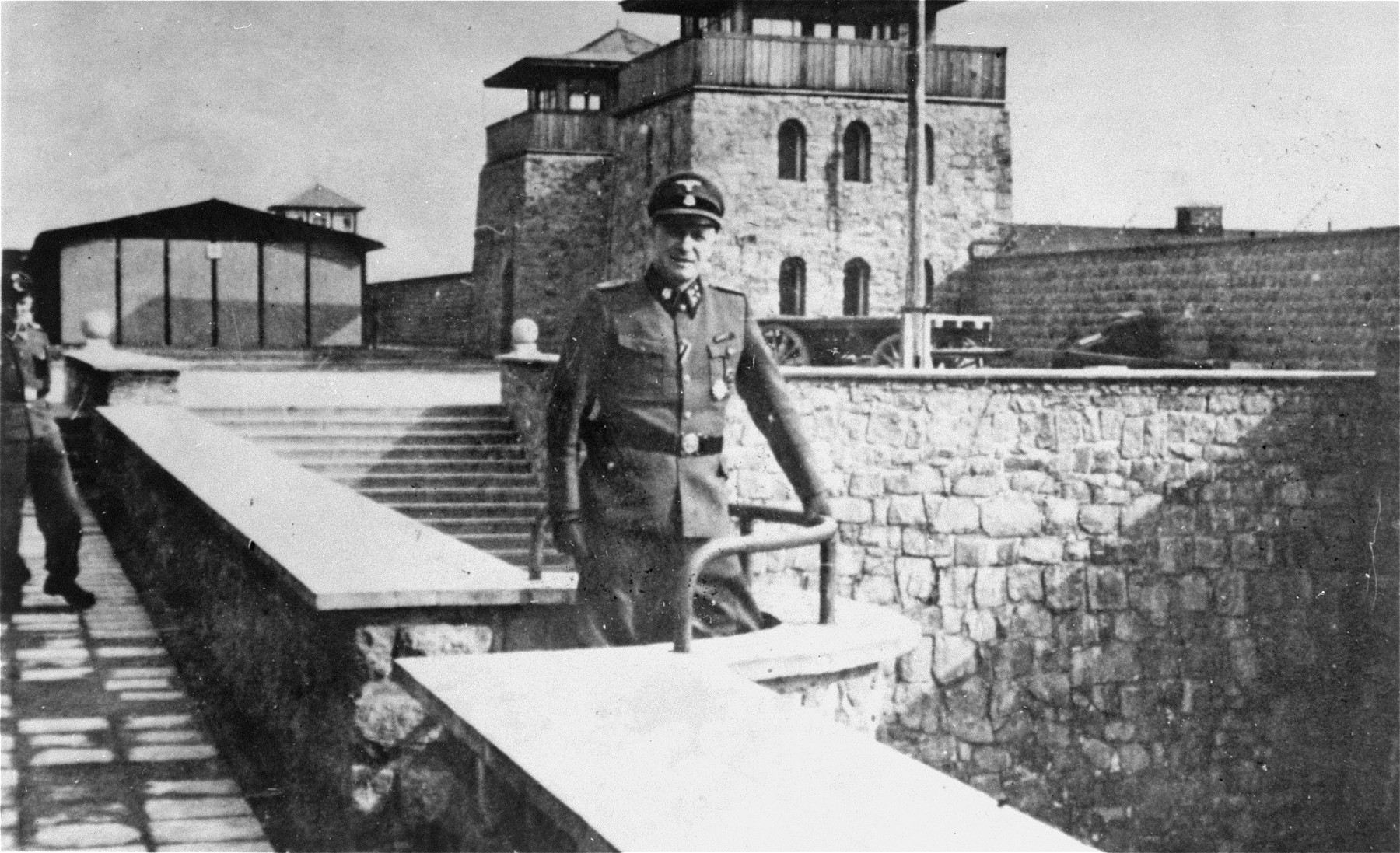 Franz Ziereis poses in front of the commandant's headquarters on the wall overlooking the garage courtyard (Garagenhofmauer) in Mauthausen.