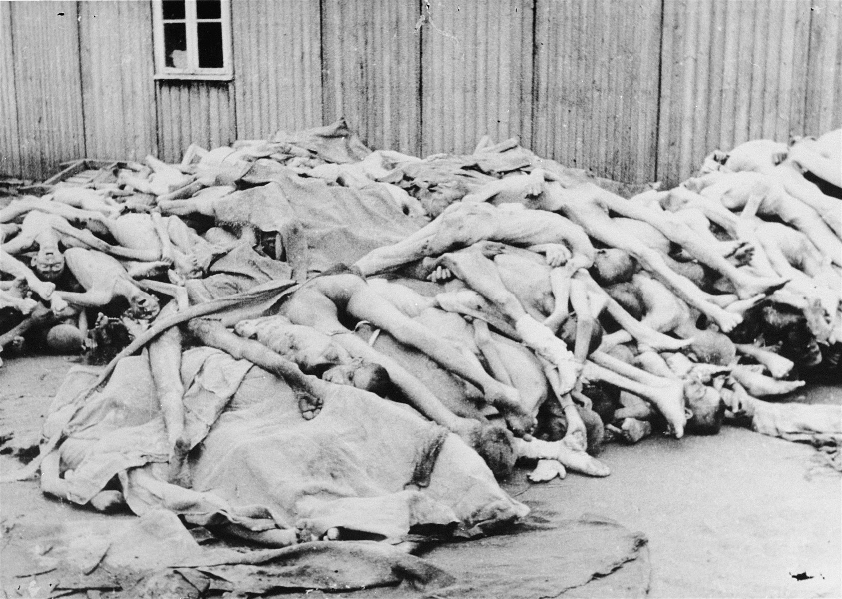 """View of 180 corpses piled outside a barracks in the """"Russian camp"""" section of Mauthausen after liberation."""