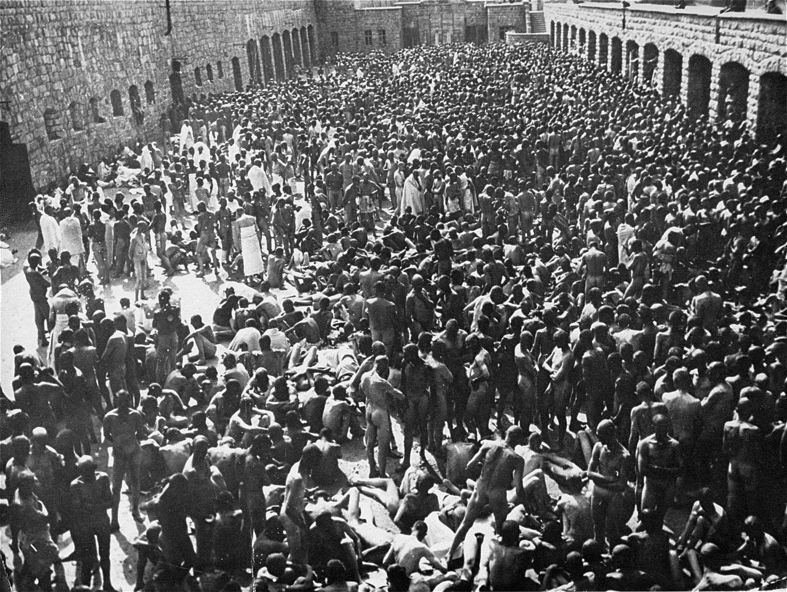 6,000 naked prisoners are assembled in the courtyard of the Mauthausen concentration camp where they await disinfection.