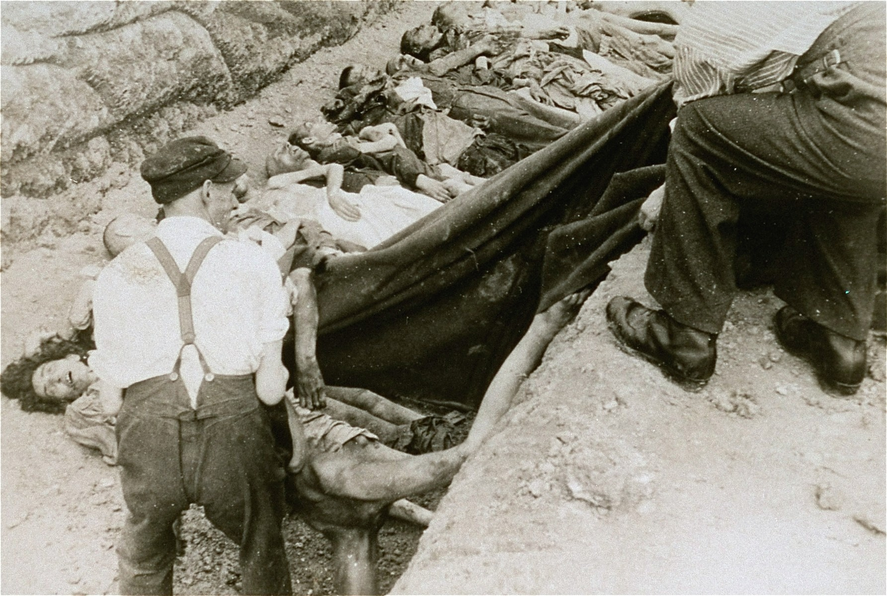 Austrian civilians lay the bodies of former inmates in a mass grave in the Mauthausen concentration camp.